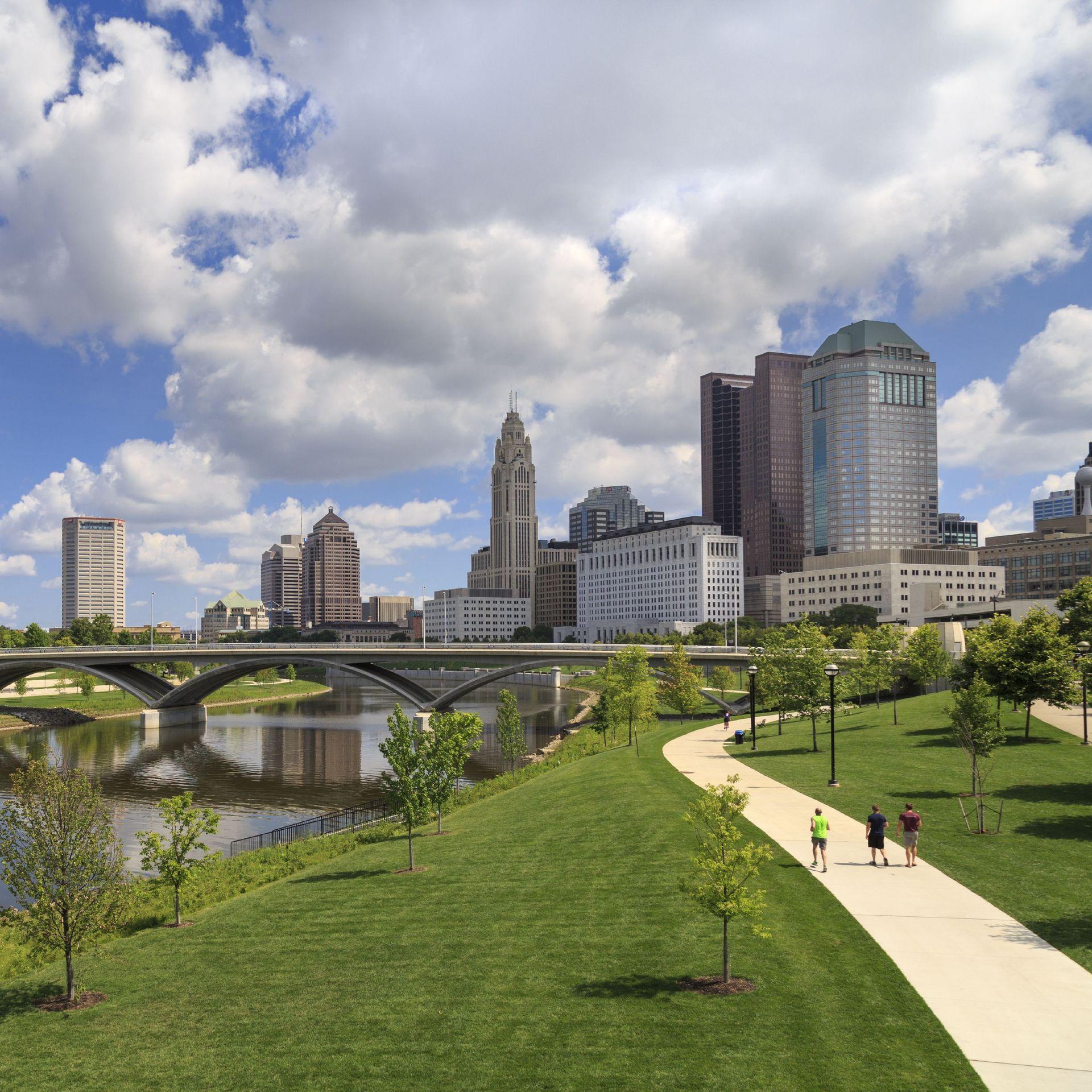 The Columbus, Ohio skyline, with a park, river, bridges and distant buildings.