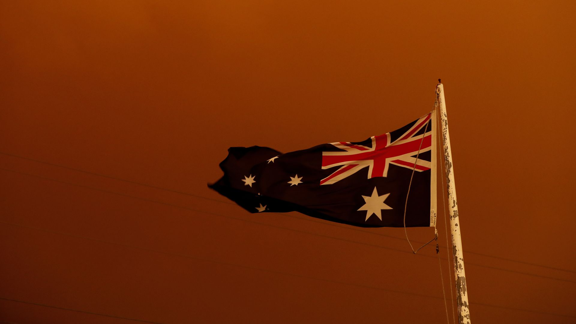 In this image, the Australian flag is seen behind a red sky.
