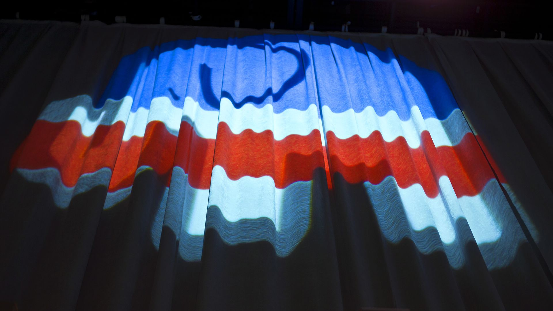 Lights reflected on a curtain reveal the shape of the GOP elephant