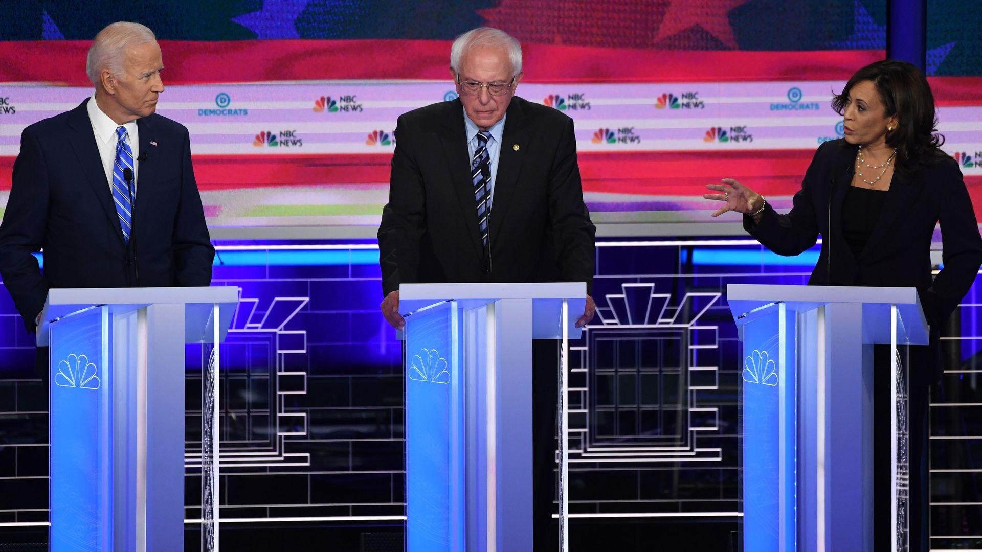 In this image, Bernie Sanders stands between Joe Biden and Kamala Harris.