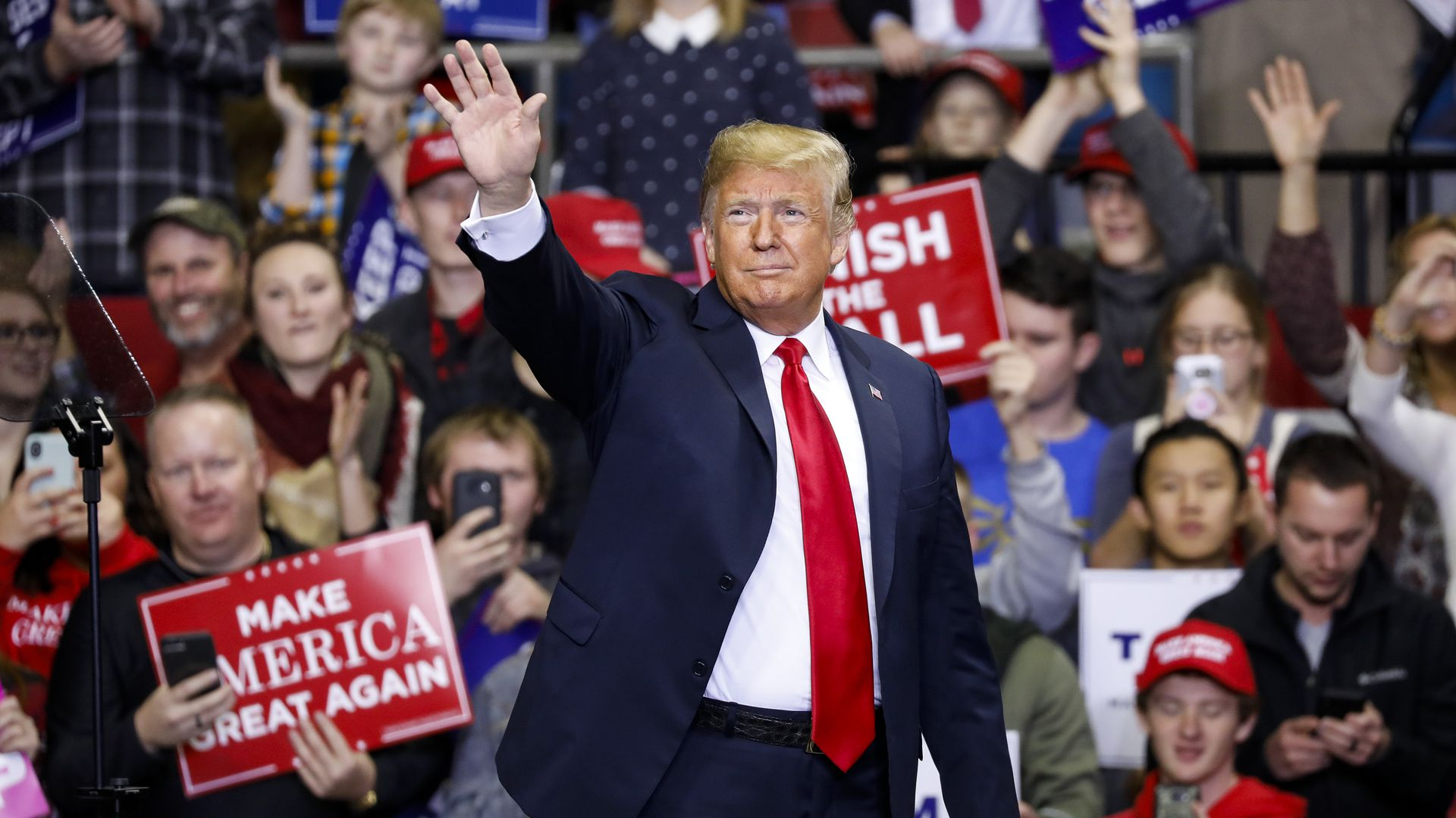 President Donald Trump waves while walking onto the stage at a MAGA rally