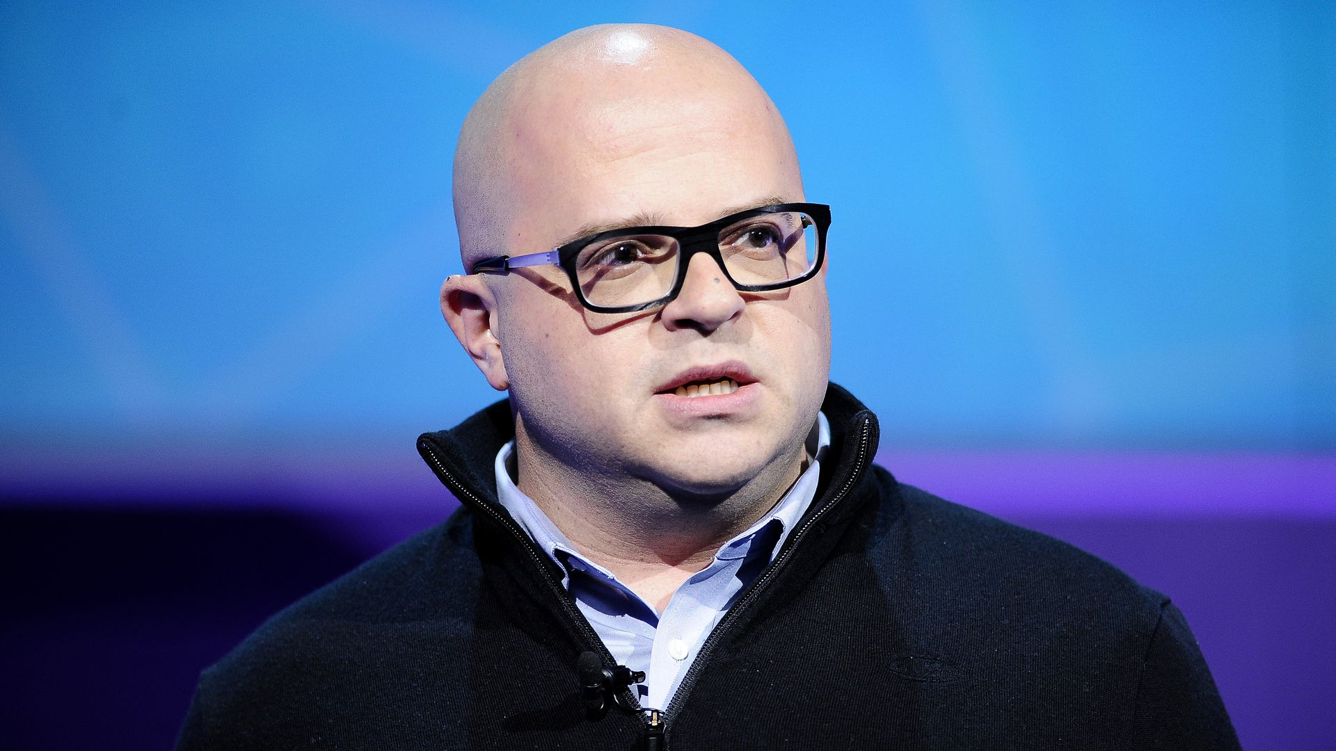 Jeff Lawson, founder, CEO and chairman of Twilio talking on a stage with blue back lighting