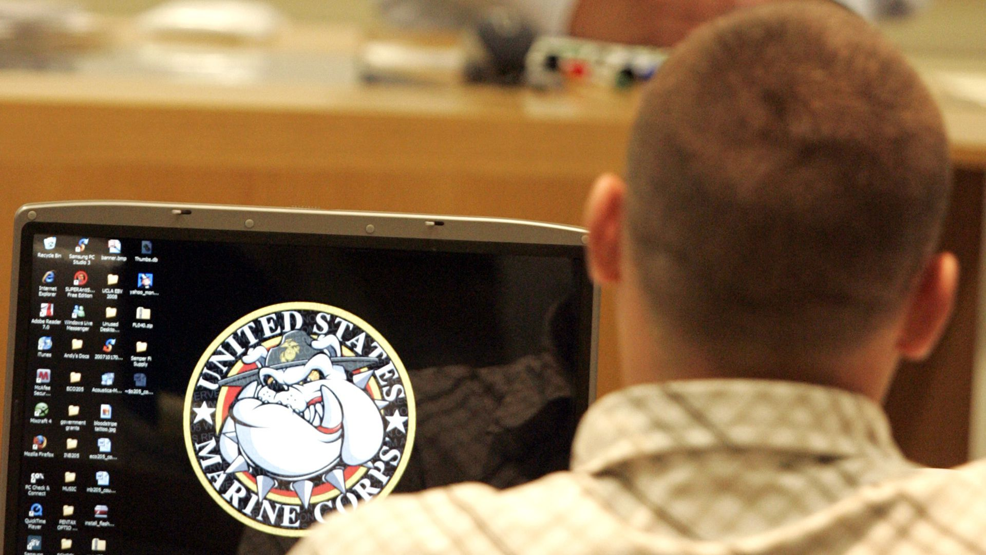 A man sits at a laptop displaying the US Marine Corps logo.