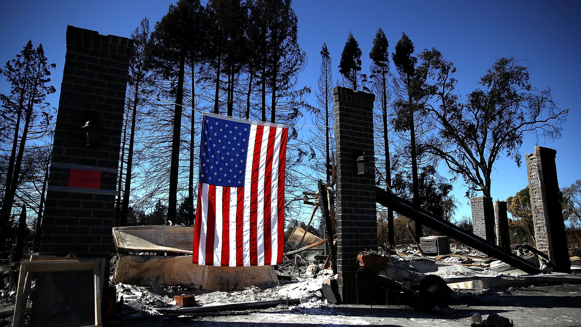 An American flag hangs in front of a home that was destroyed by a wildfire in California.