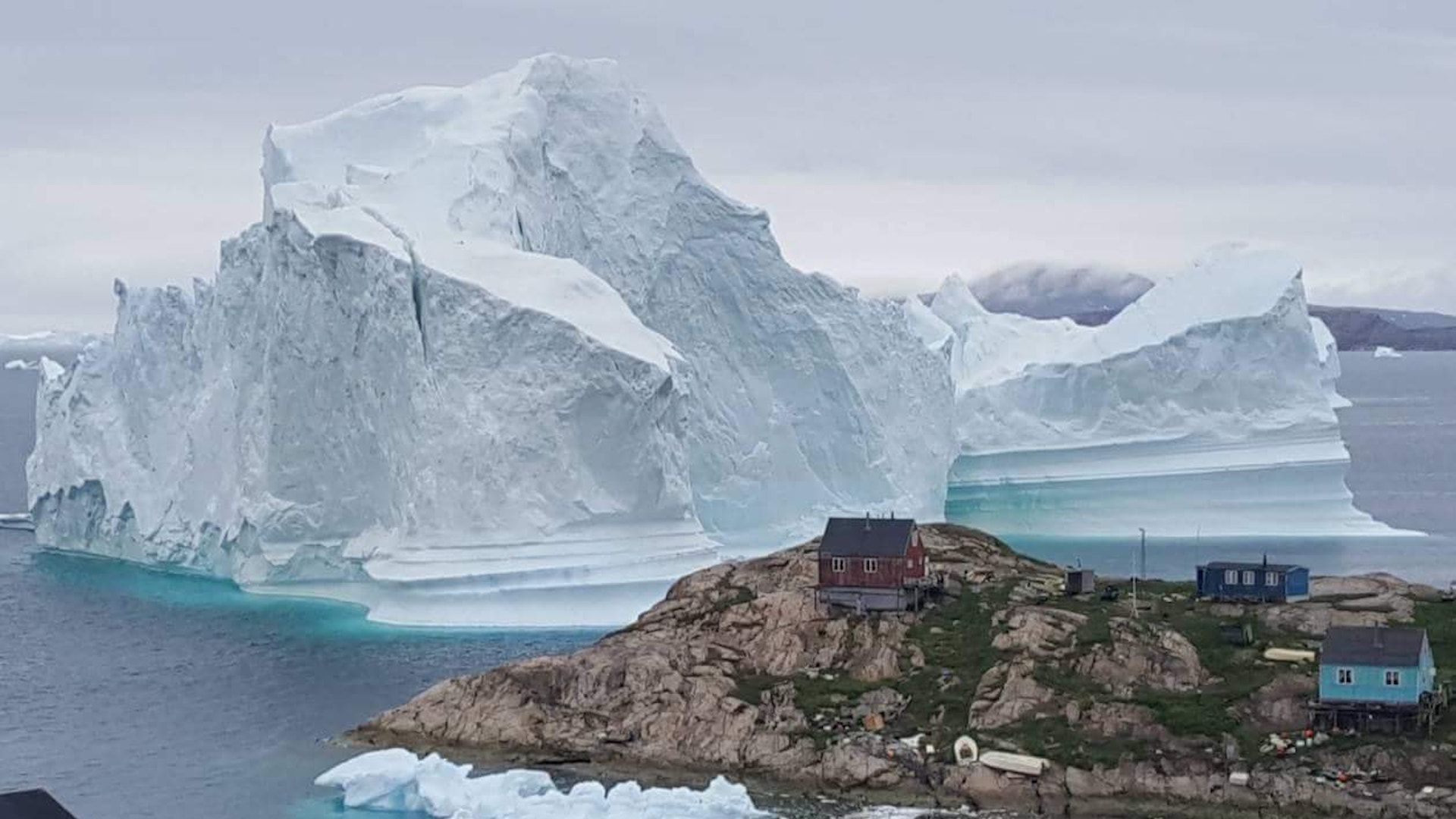 A picture taken on July 13, 2018 shows an iceberg behind houses and buildings after it grounded outside the village of Innaarsuit, Greenland.