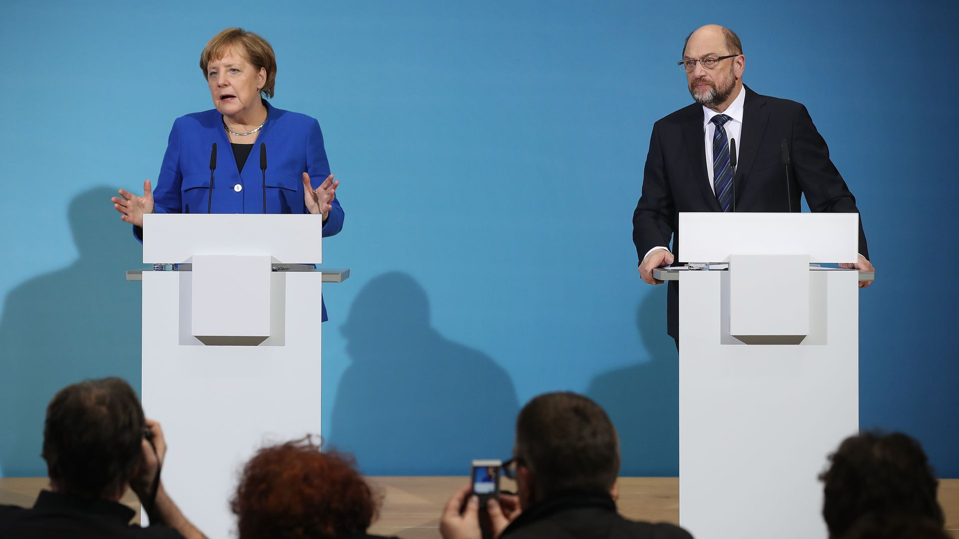 Angela Merkel and Martin Schultz speak at podiums