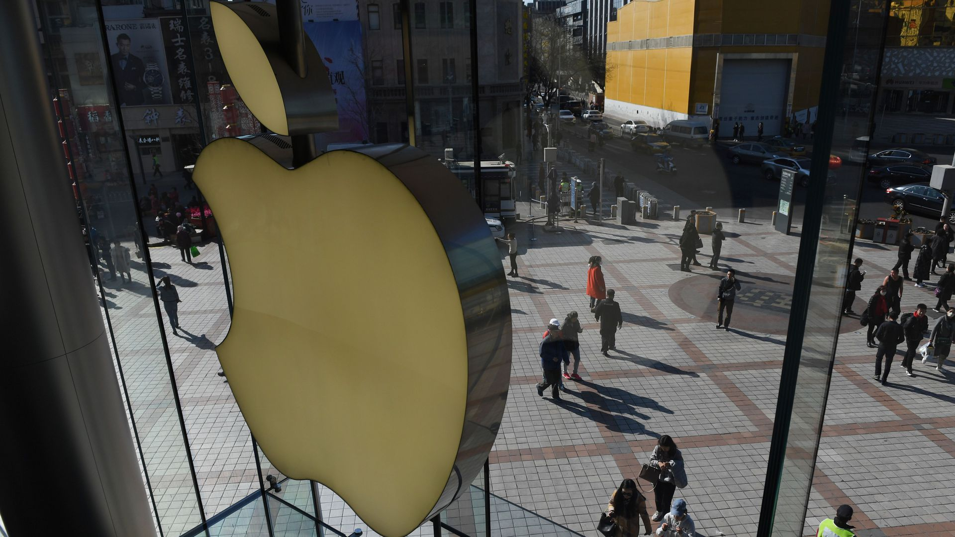 In this image, the Apple logo is displayed over a city walkway with a few pedestrians.