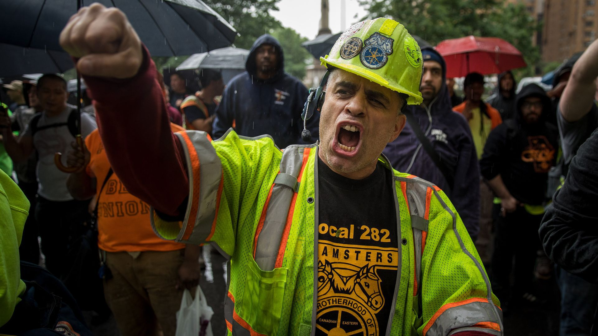 A construction worker protests with his fist in the air