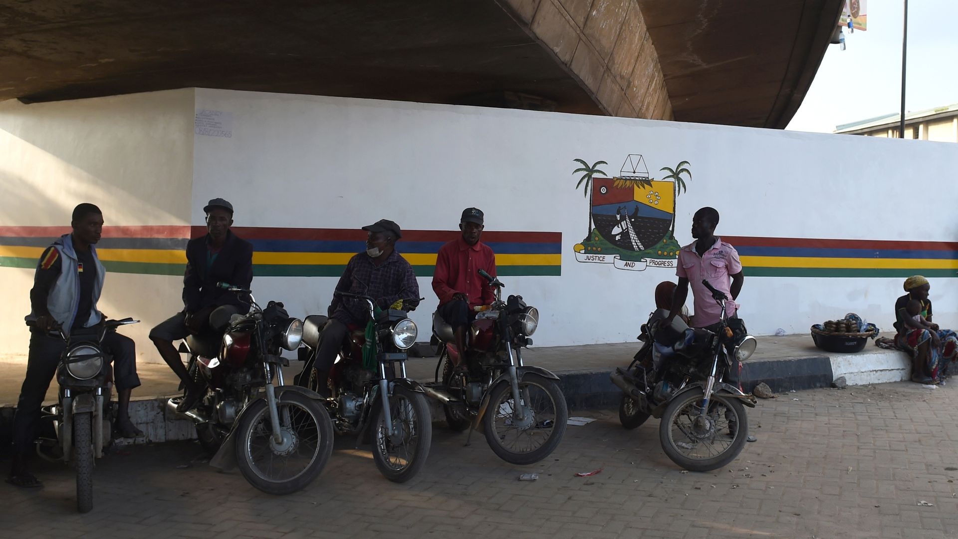 motorbike taxis waiting for passengers in the shade under an overpass