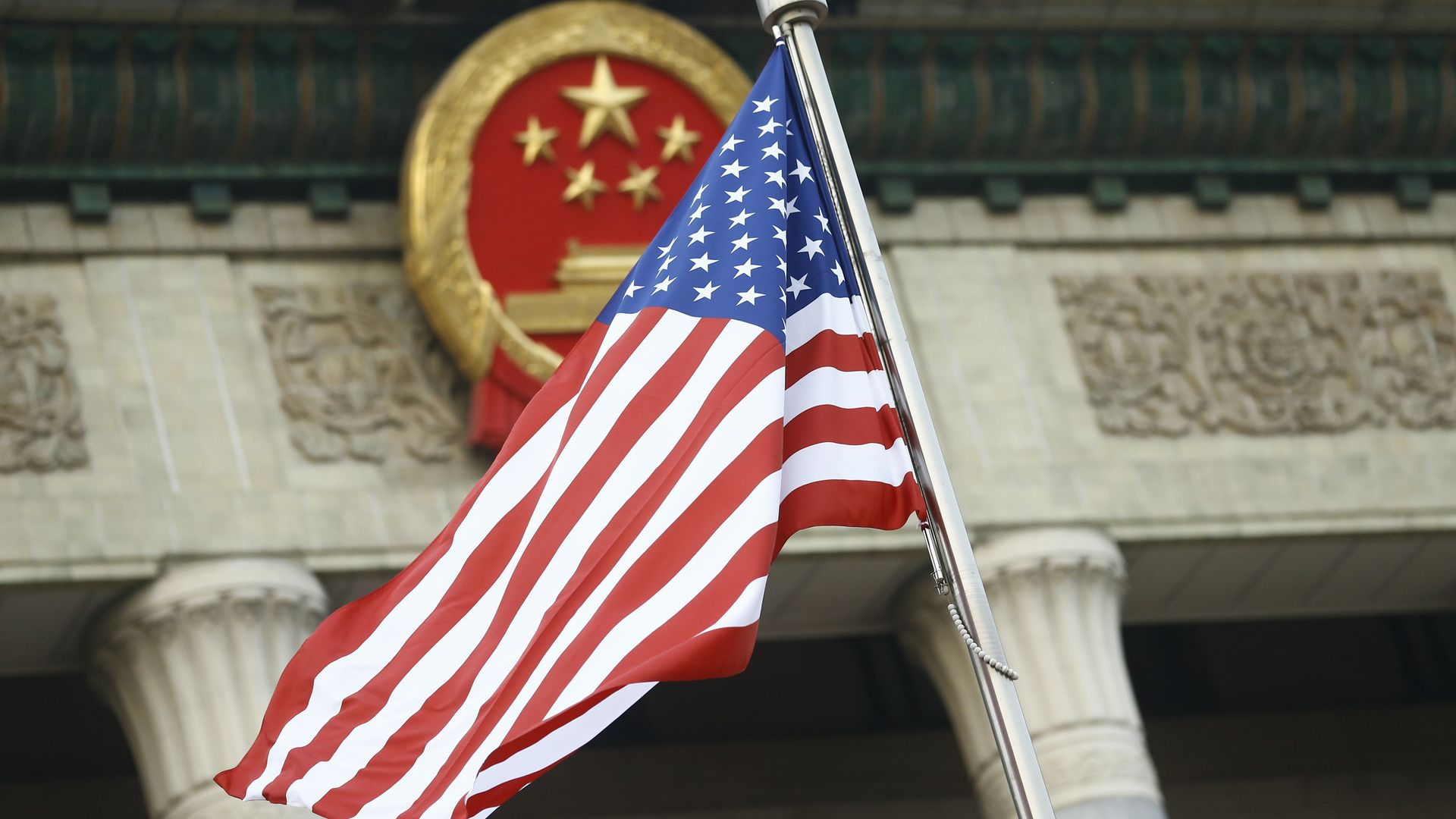 An American flag flies in front of a Chinese emblem.