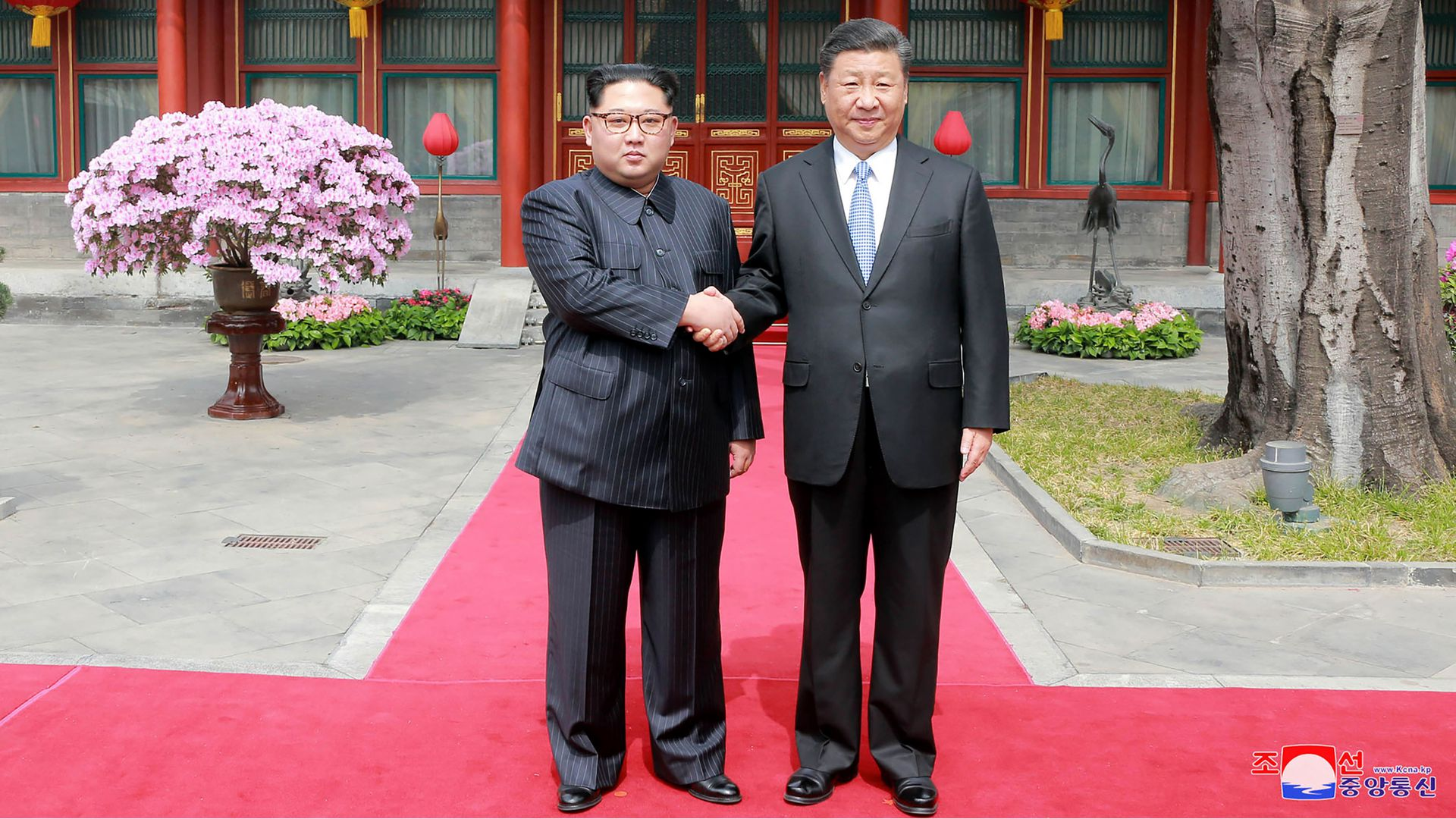 Kim Jong-un and Xi Jinping are shaking hands in the middle of the photo.