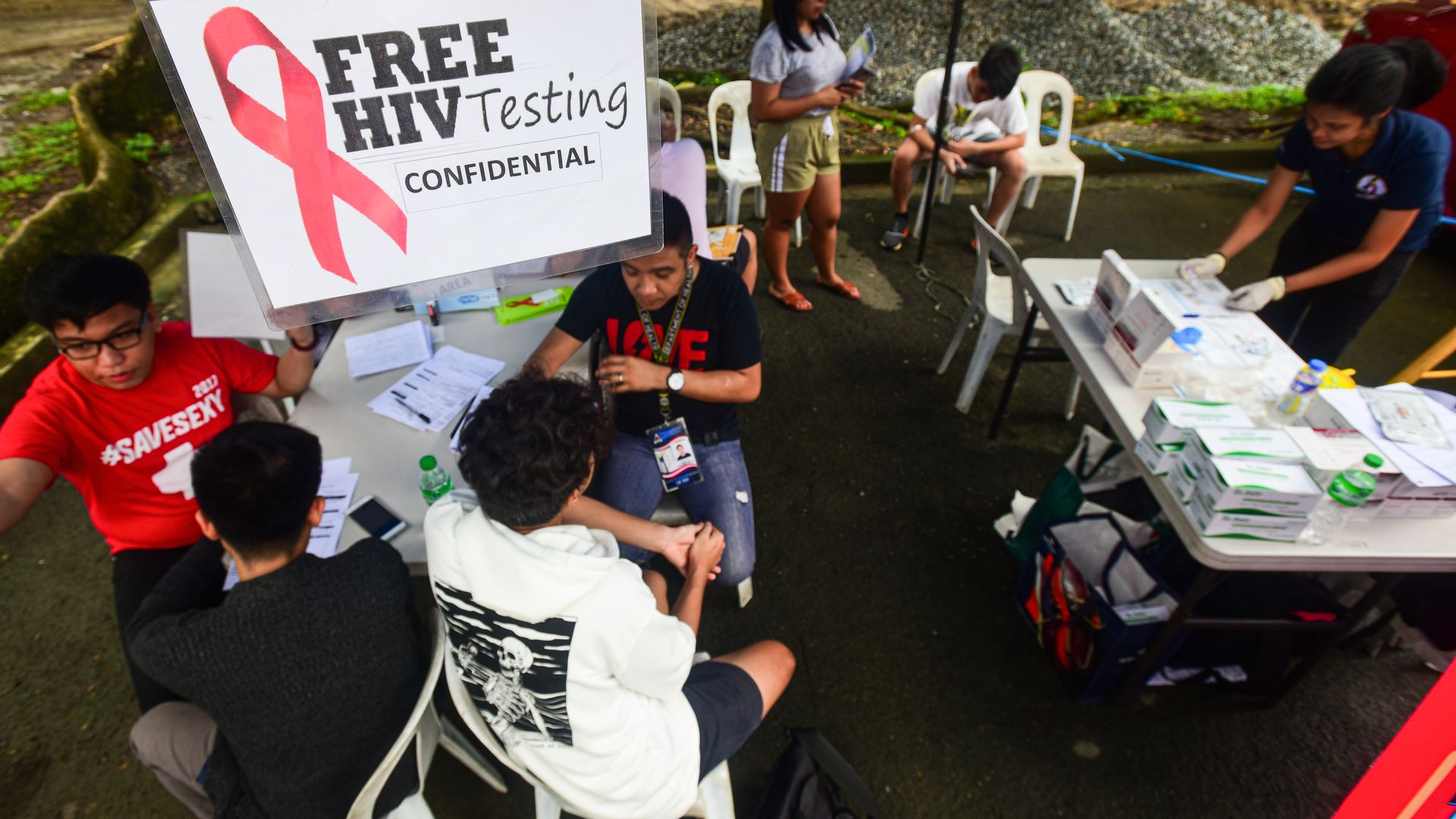 Medical technologists speak to people about free HIV testing in Manila.