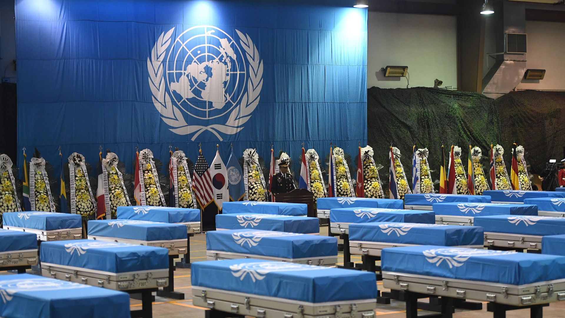 Caskets covered in blue sheets at a UN repatriation ceremony