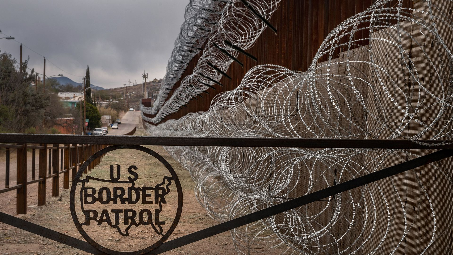 A metal fence marked with the US Border Patrol sign prevents people to get close to the barbed/concertina wire covering the US/Mexico border fence, in Nogales, Arizona, on February 9, 2019.