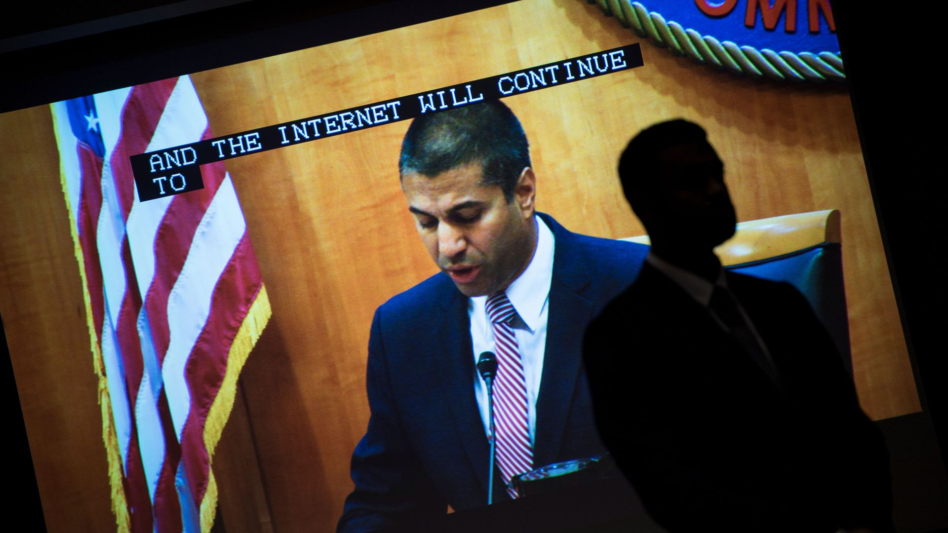 FCC Chairman Ajit Pai is shown on a screen at the agency