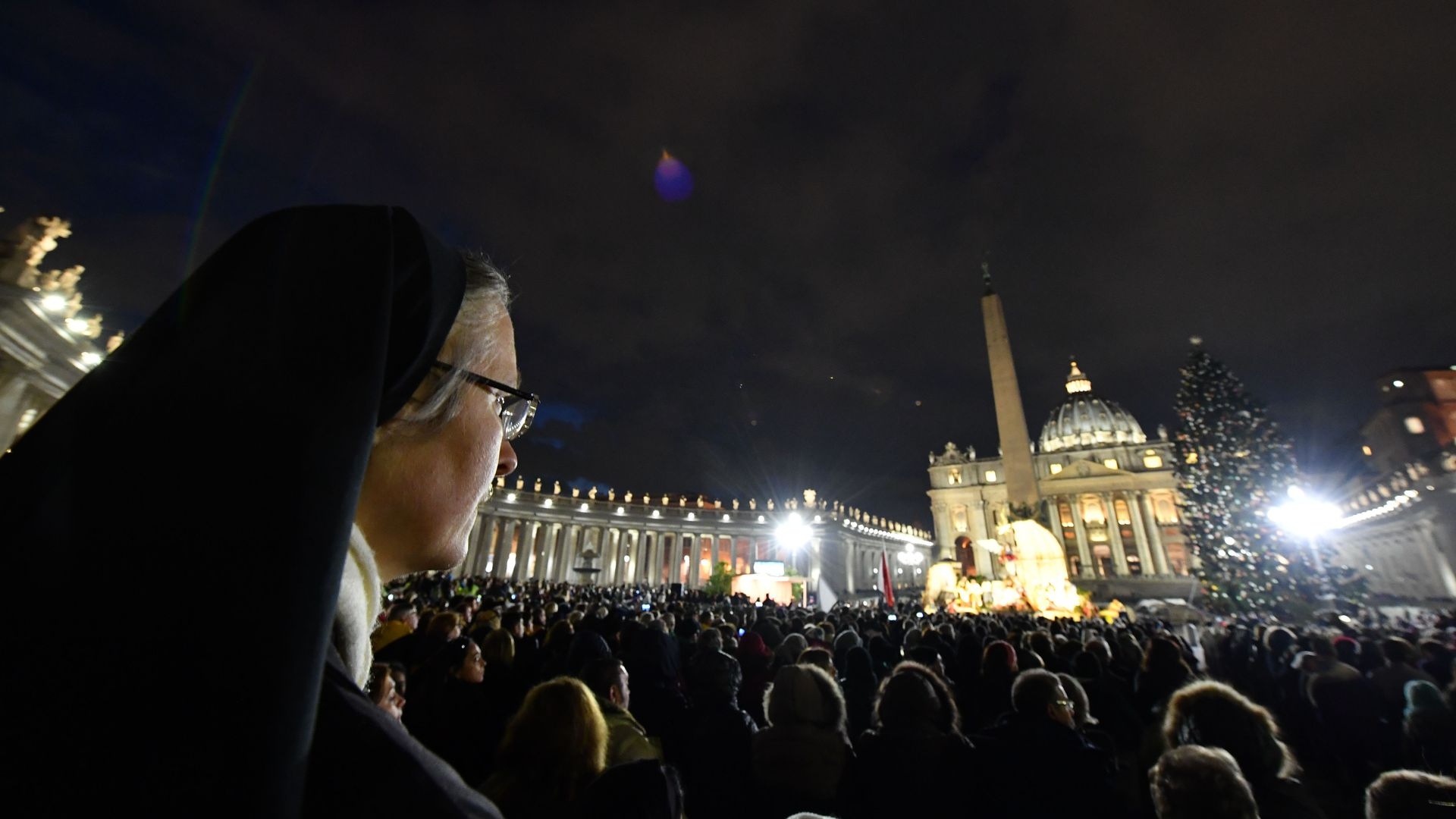 A nun in a crowd at the Vatican during Christmas.