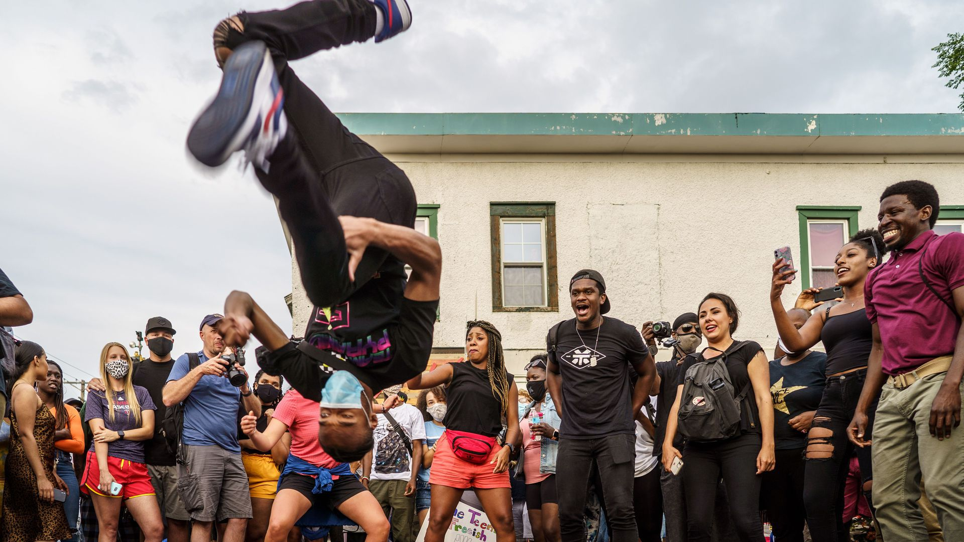 A man doing a backflip and people celebrating Juneteenth last year in George Floyd Square.