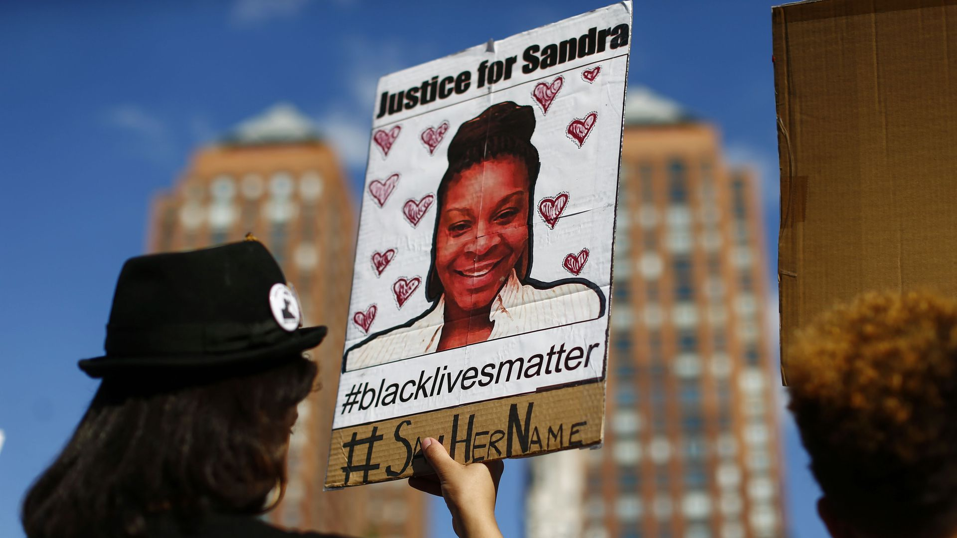 Protestor holds a portrait of Sandra Bland.
