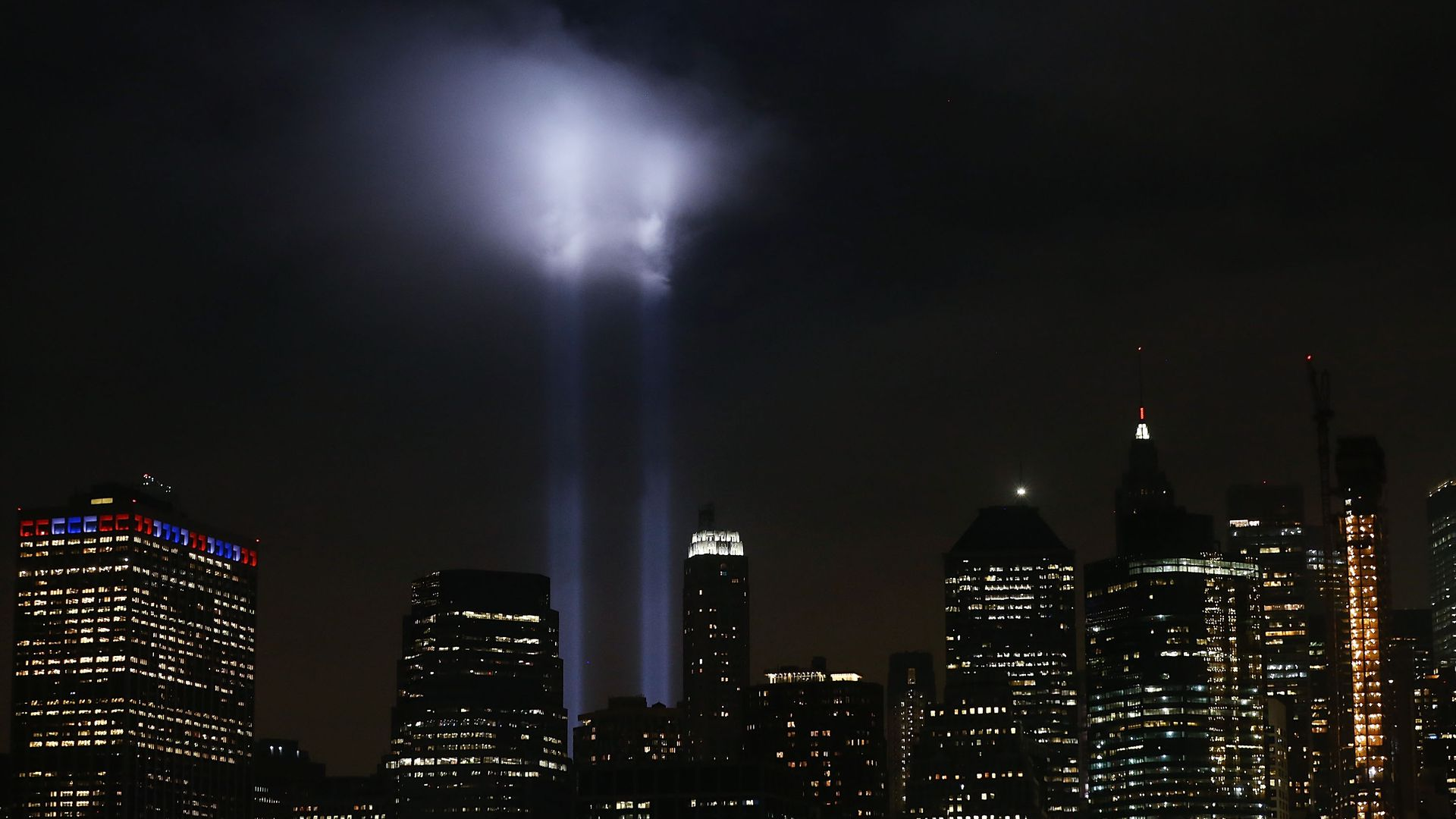 Twin towers' absence highlighted with spotlights in the night sky.