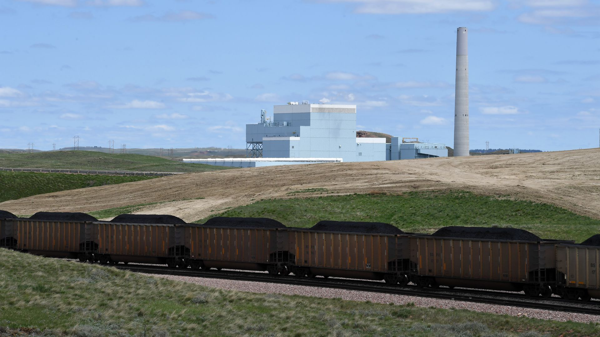 A coal train in front of a coal fired power plant.