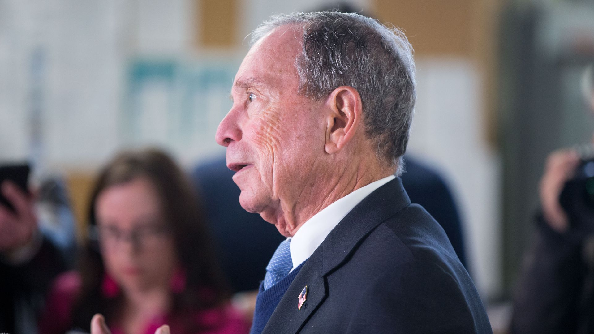This image a side profile of Bloomberg talking and wearing a suit.