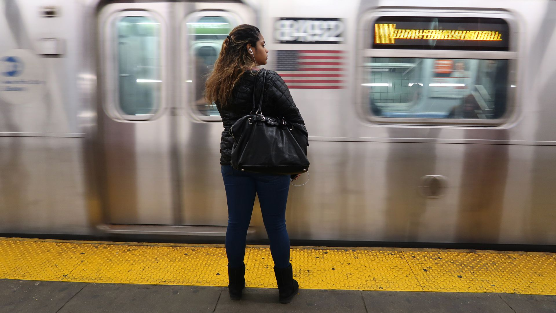 A woman stands near the yellow strip on the concrete ground as a subway train goes past her.