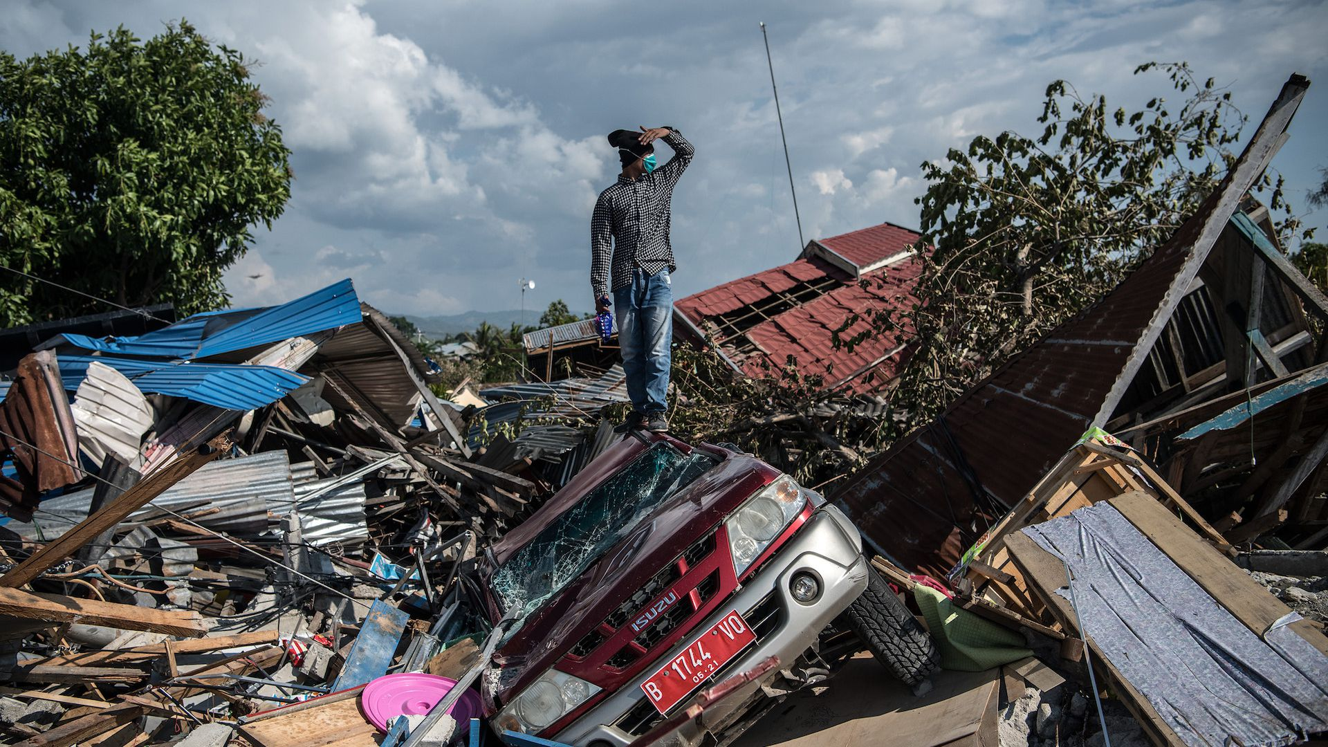 A man stands on a destroyed car as he views the rubble and debris of destroyed buildings following an earthquake in Palu, Indonesia.
