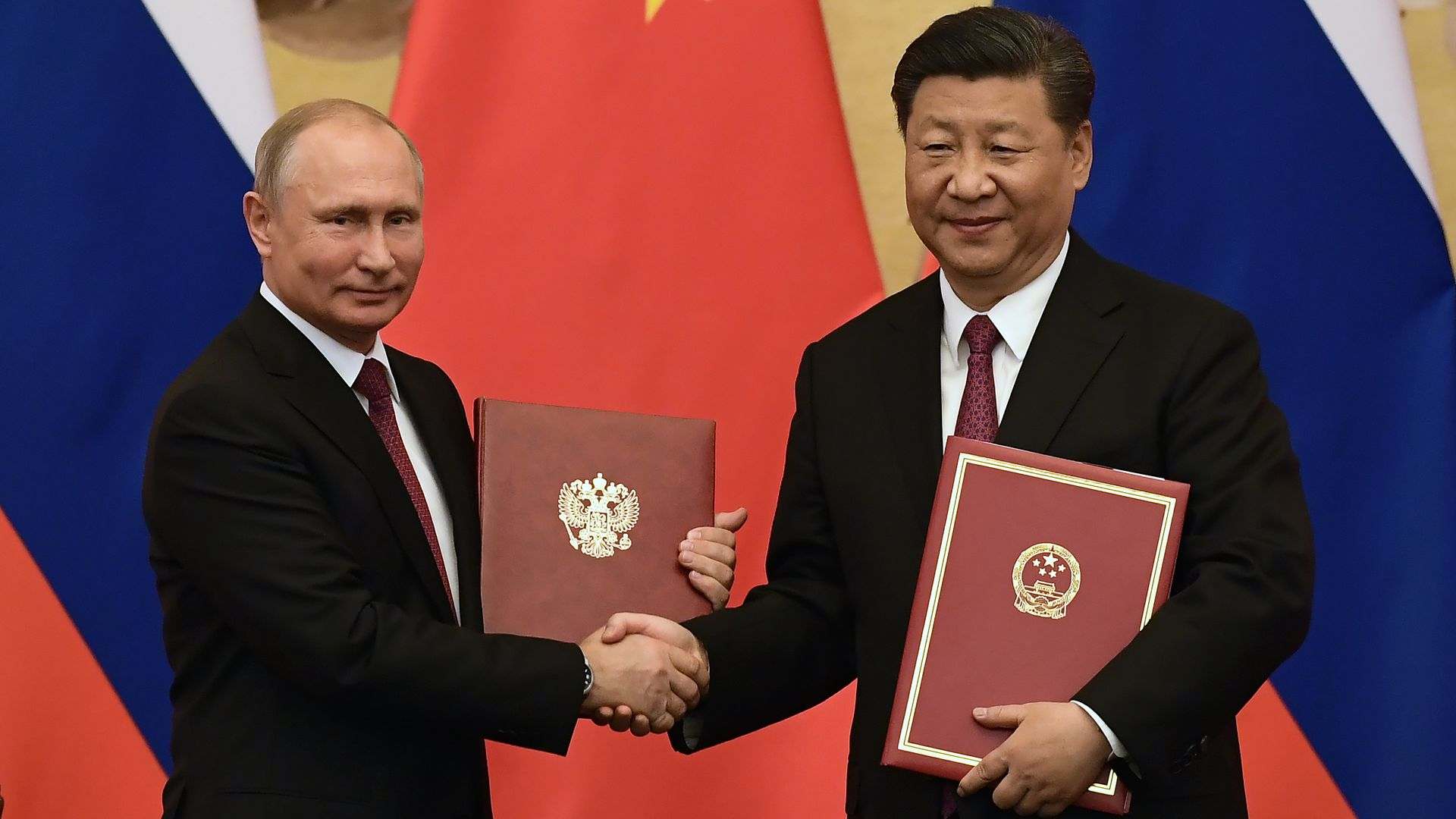 Russian President Putin shaking Chinese President Xi and getting friendship award