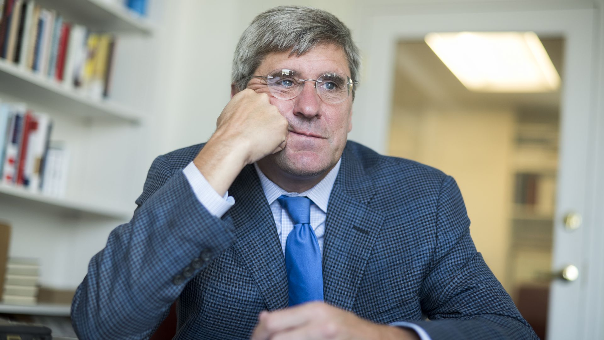In this image, Stephen Moore sits at a desk and leans his face against one hand. He's wearing glasses.