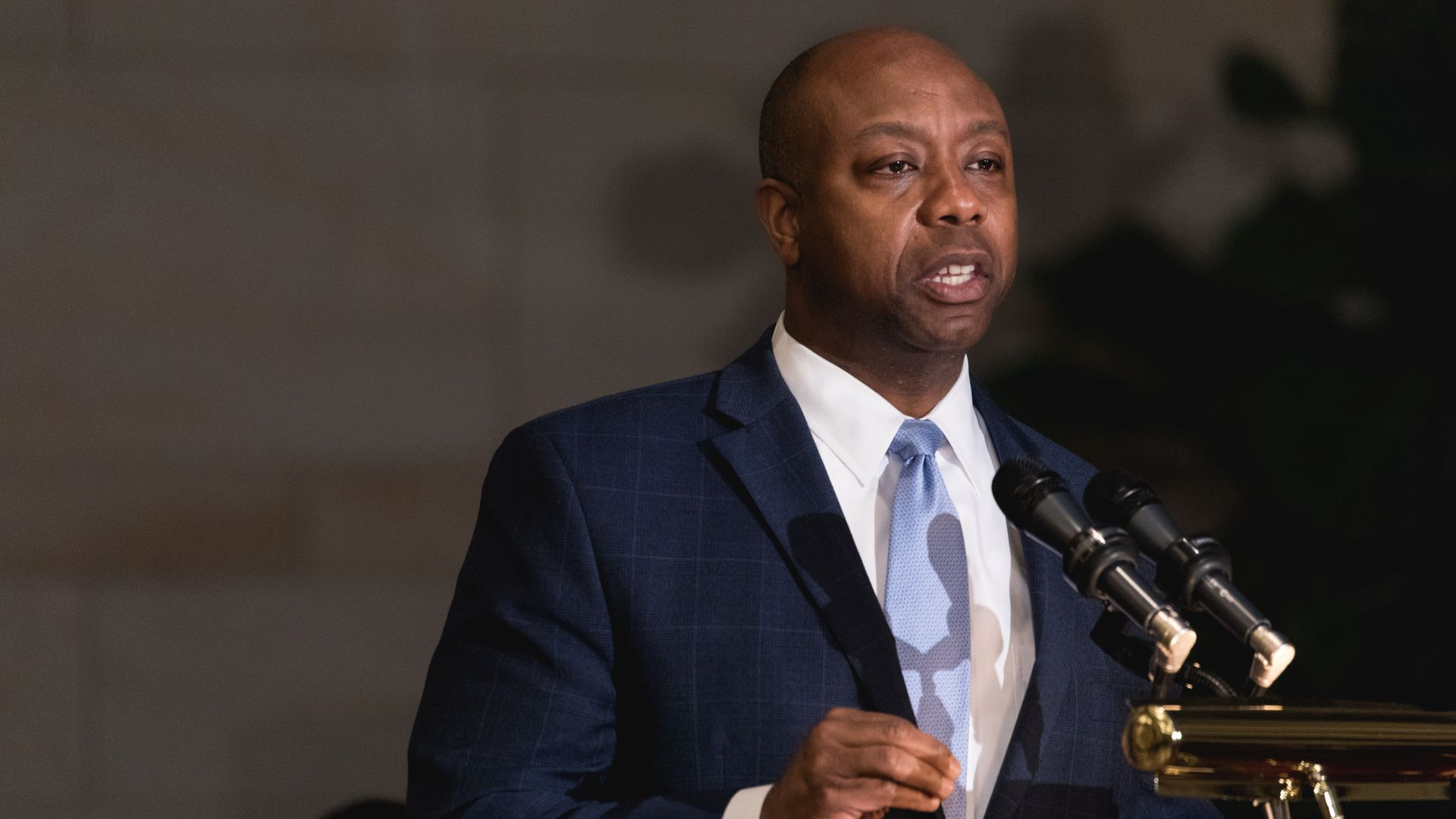 Sen. Tim Scott speaks at a podium which holds two microphones