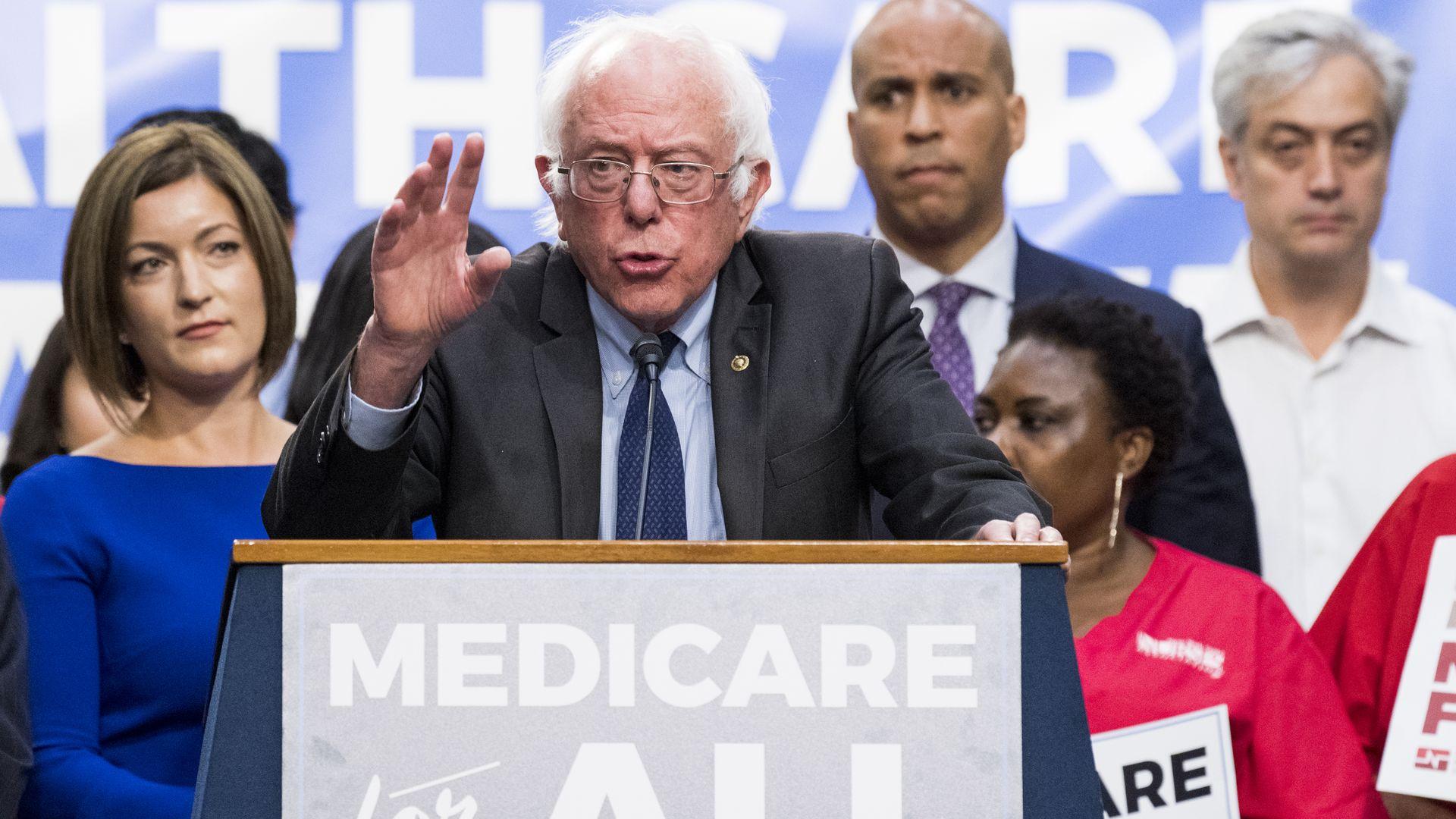 Bernie Sanders speaking behind a Medicare for All lectern