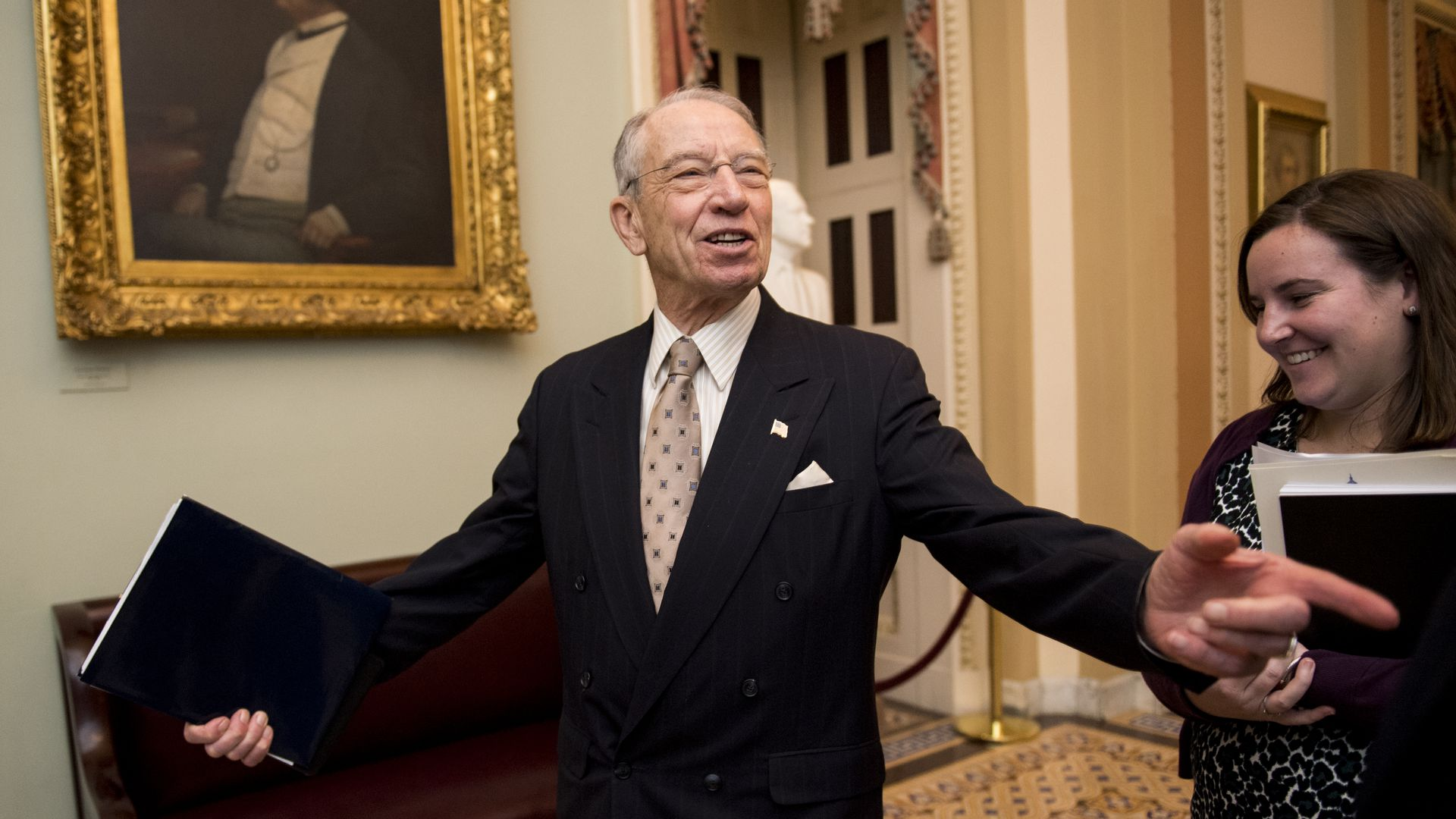 Senator Chuck Grassley, wearing a suit and tie, in the middle of an interaction with someone off-screen