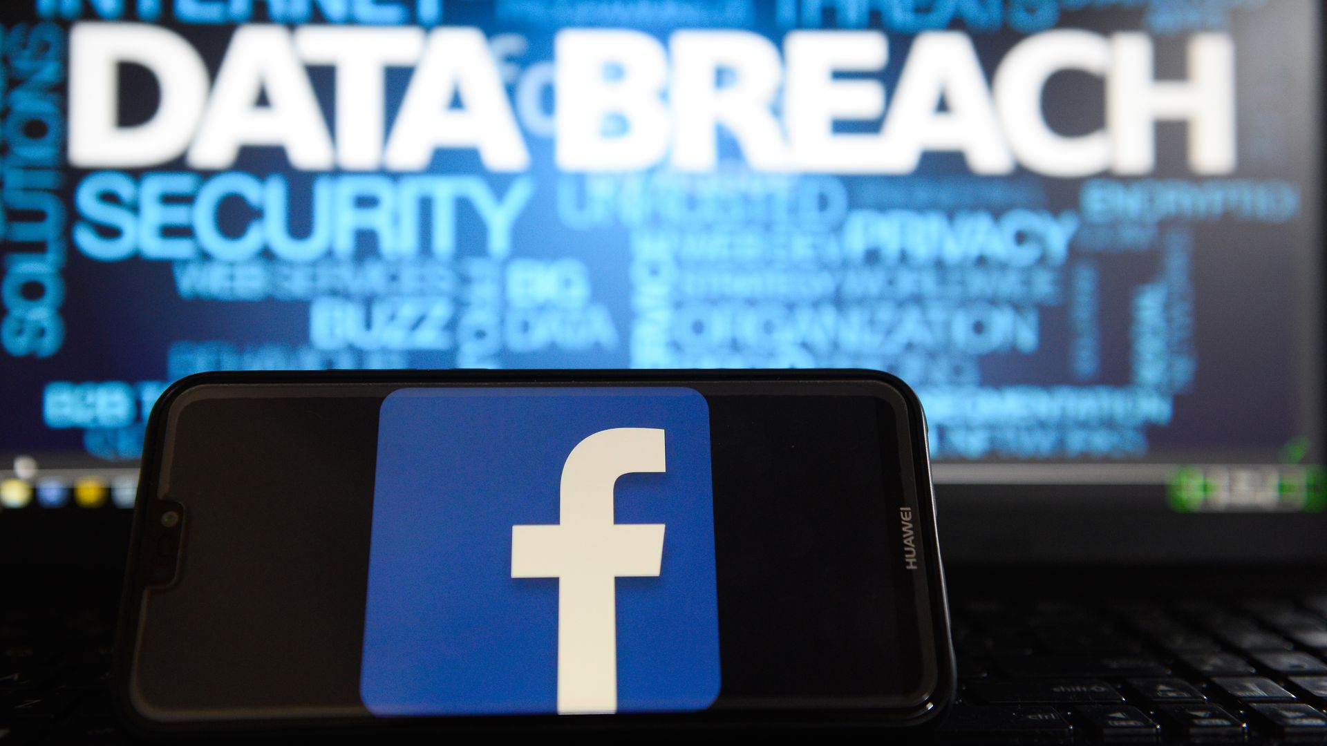 "Facebook logo is seen on a Huawei smart phone with the word ""data breach"" on a laptop monitor."