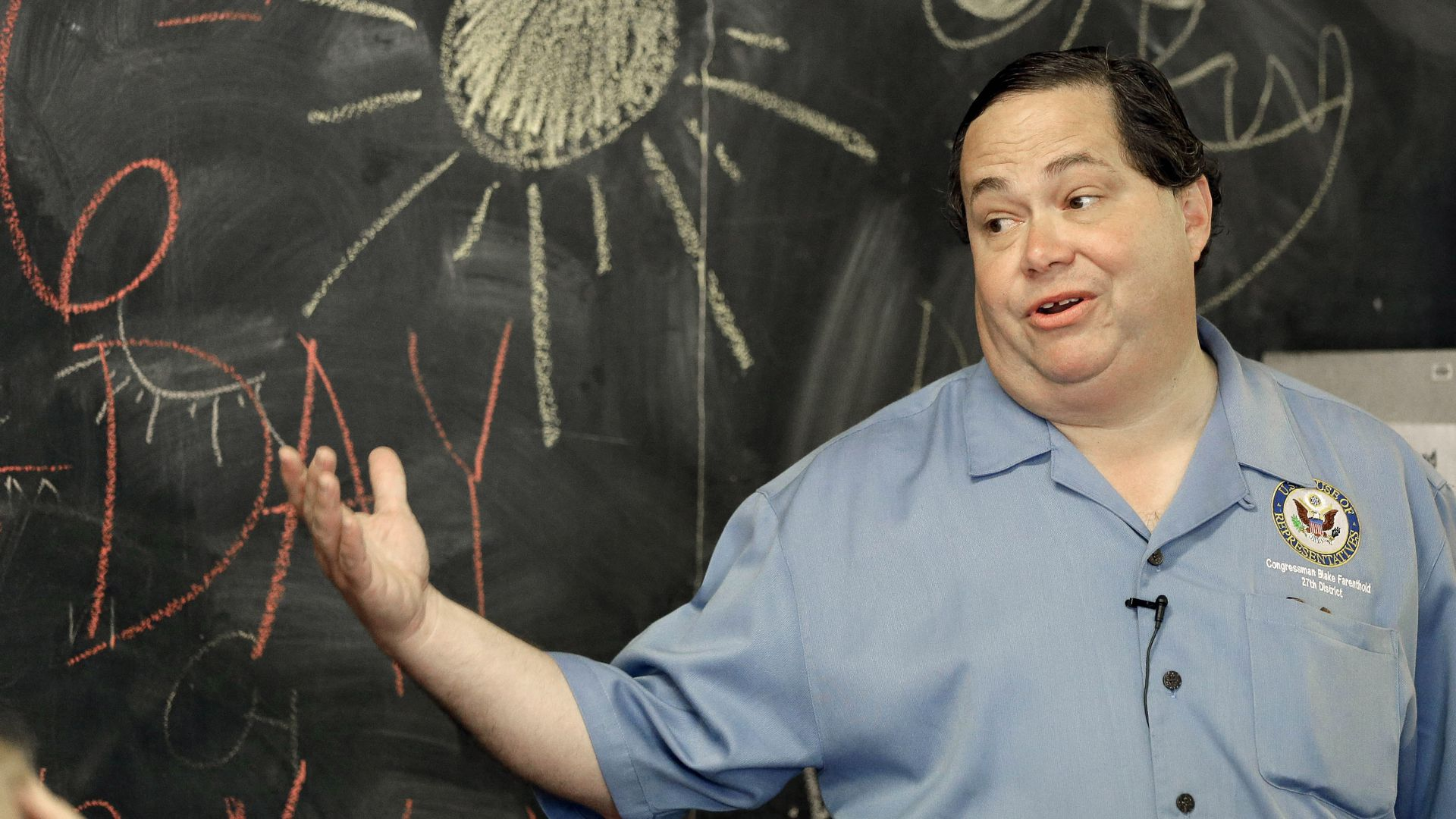 Rep. Blake Farenthold in front of a chalkboard with a yellow sun drawn on it with chalk.