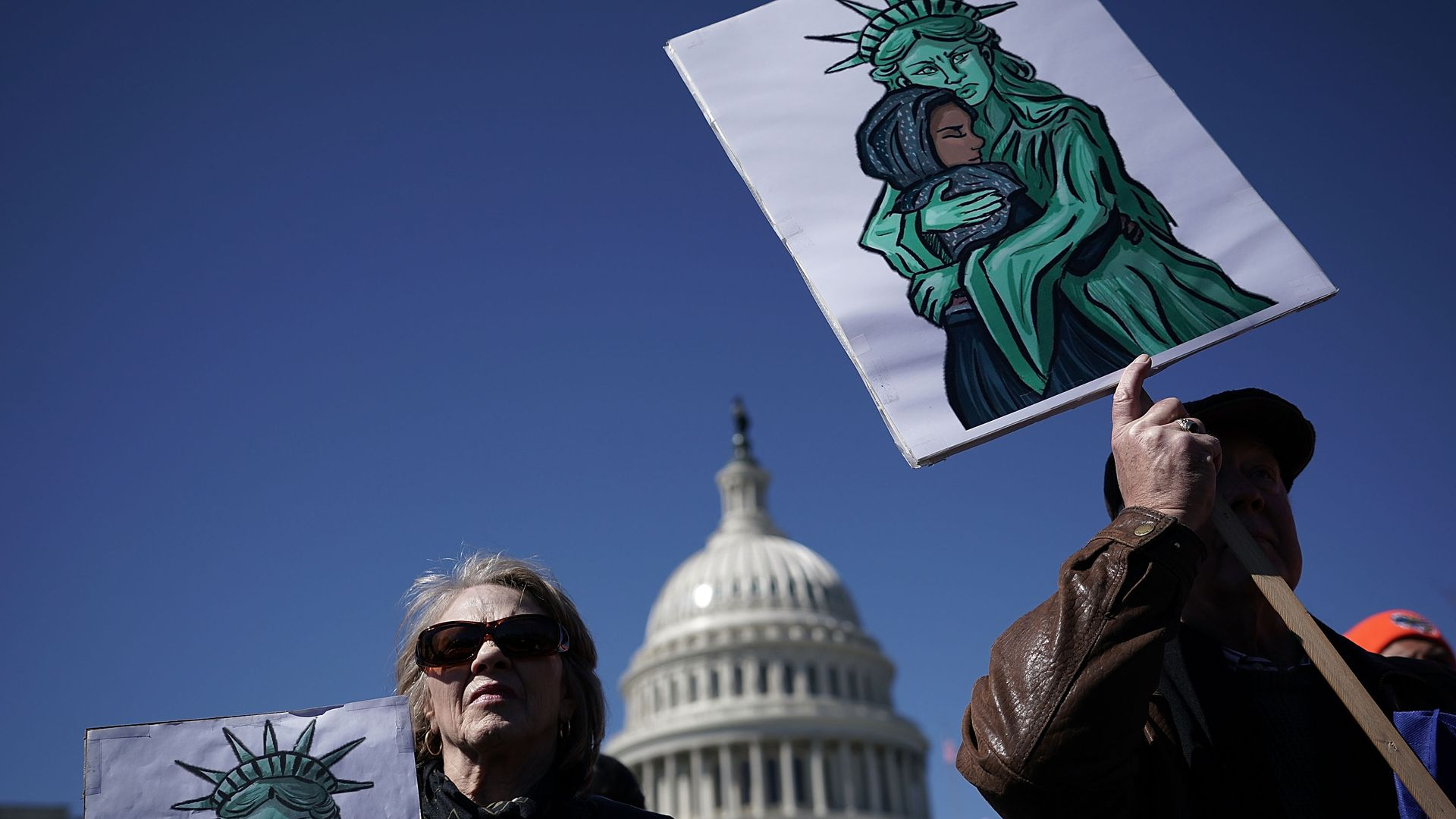 Two protestors holding signs of the statue of liberty hugging a woman with a hijab. The capitol building is in the background.