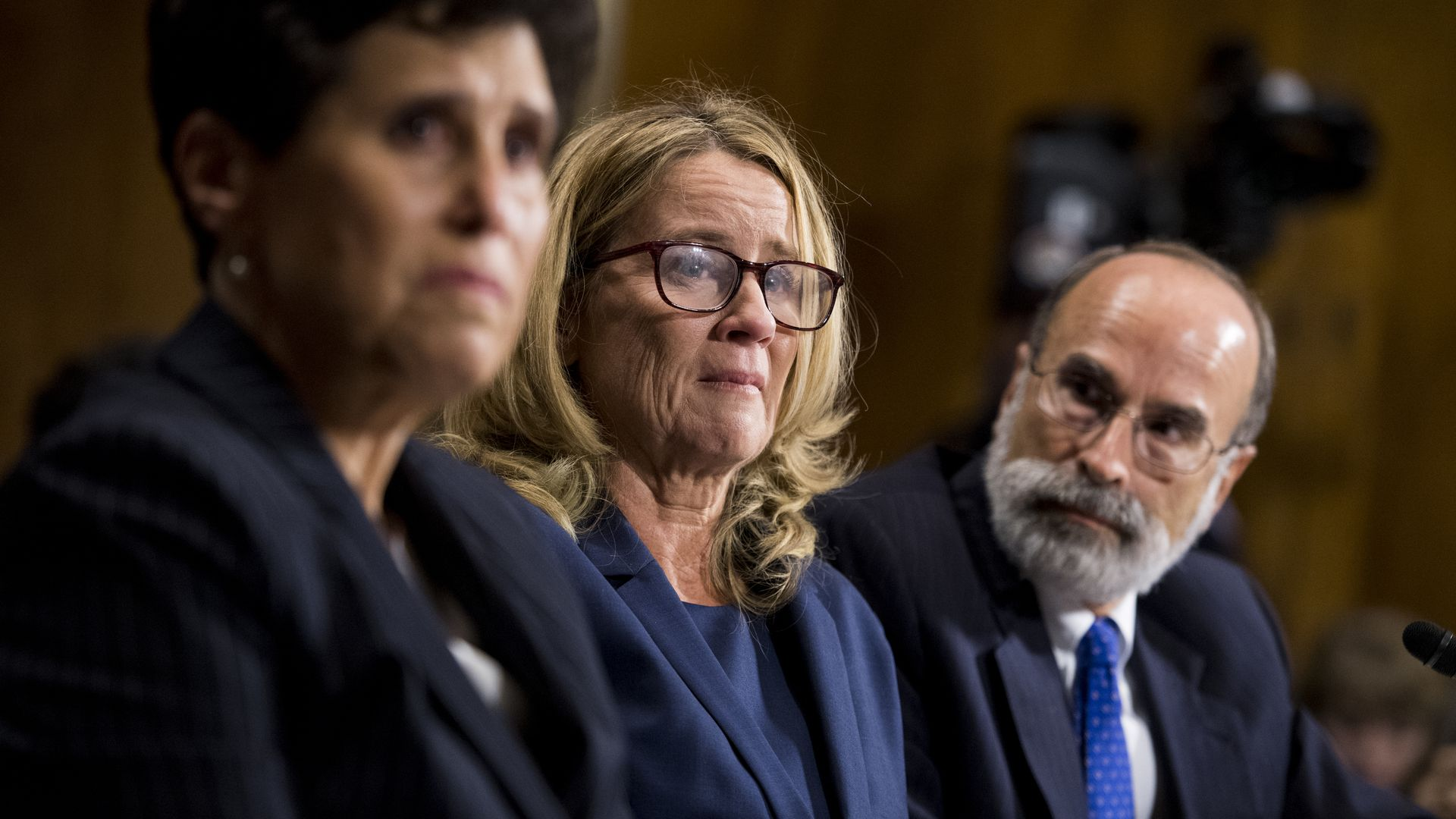 Christine BLasey Ford sits in a senate hearing next to her lawyers.