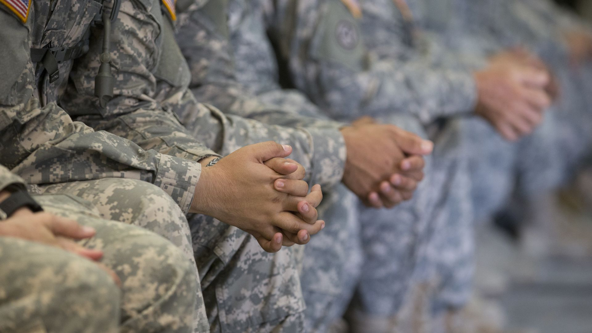 National Guard troops' hands clasped together as they sit in a row in uniform.
