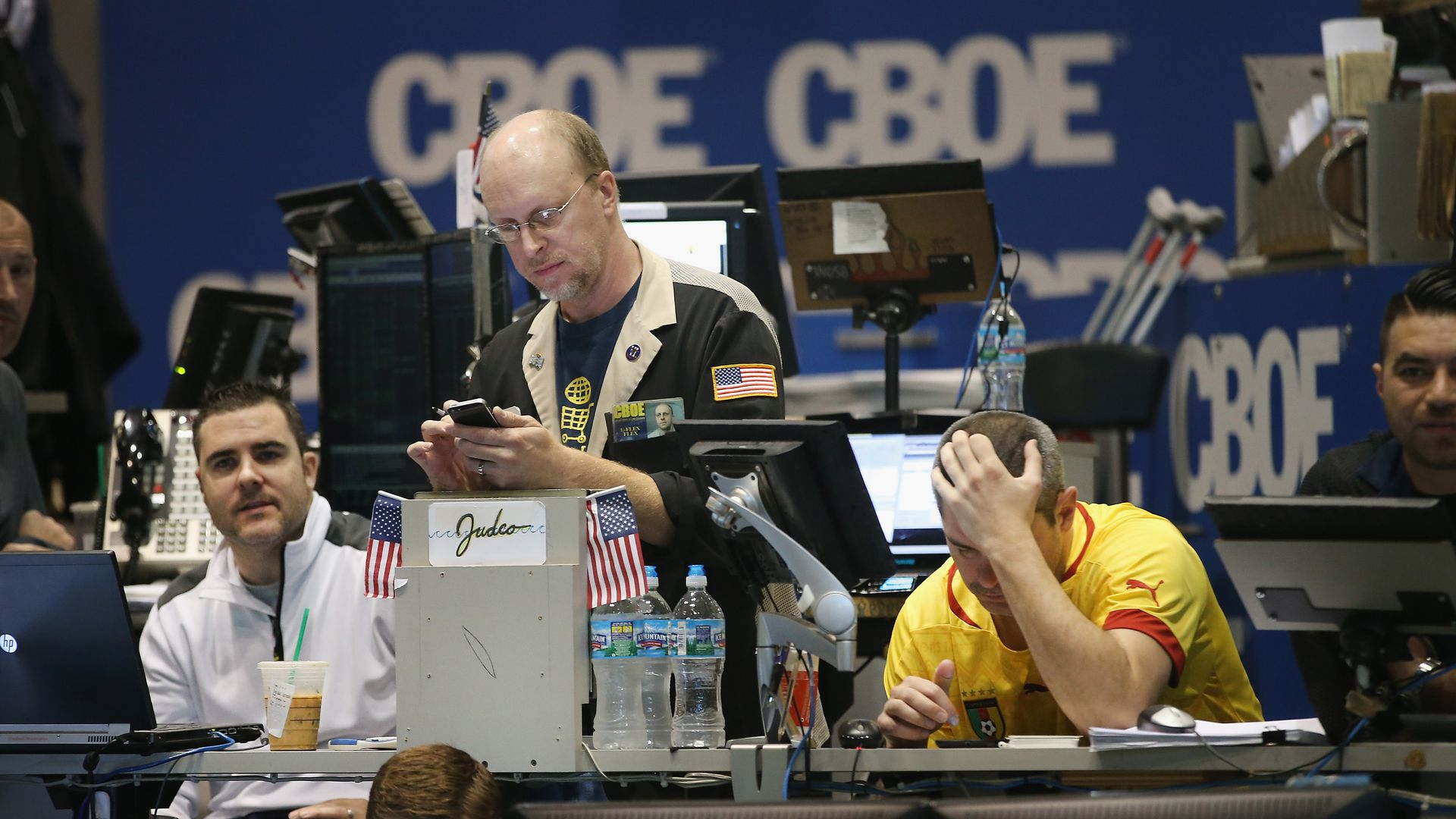 In this image, two men sit behind computers on a trading floor and one man stands between them, looking at his phone.