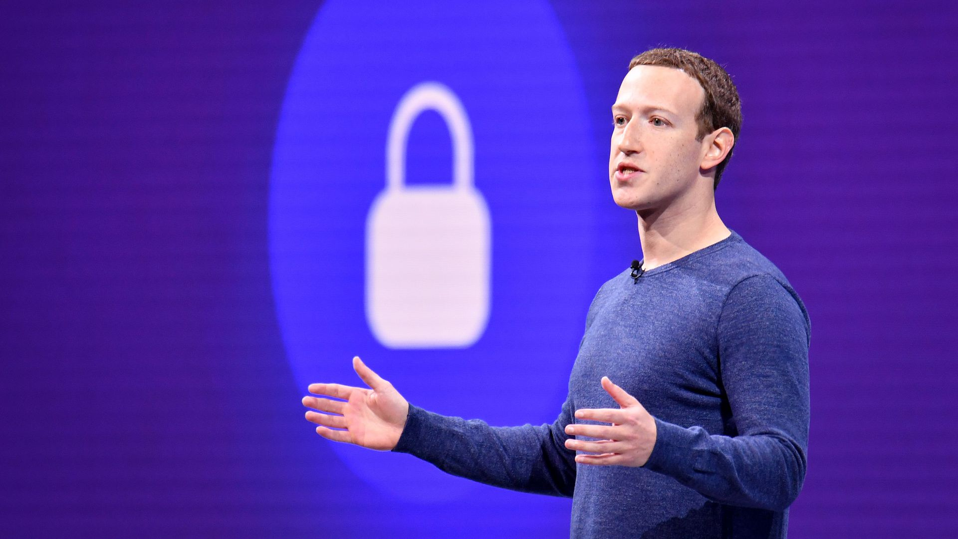 Photo of Facebook CEO Mark Zuckerberg with arms out and a lock icon projected behind him on stage