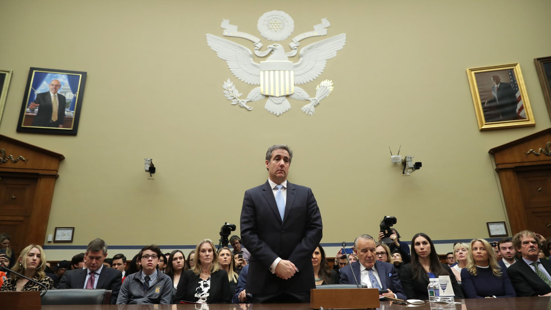 In this image, Michael Cohen stands with his hands folded in court and looks down.