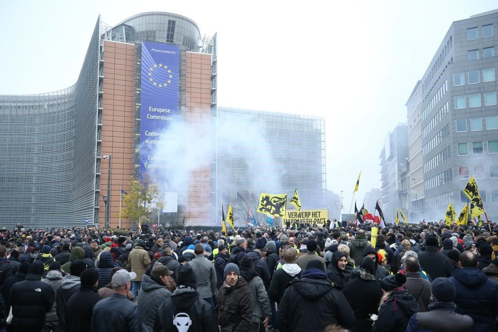 Around 1,000 far-right, anti-migration protesters gather for a demonstration as police officers intervene them with teargas near EU buildings in Brussels on Sunday.