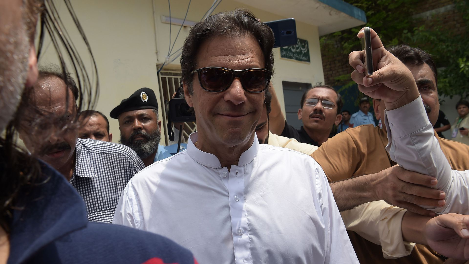 Imran Khan smiling with sunglasses on.