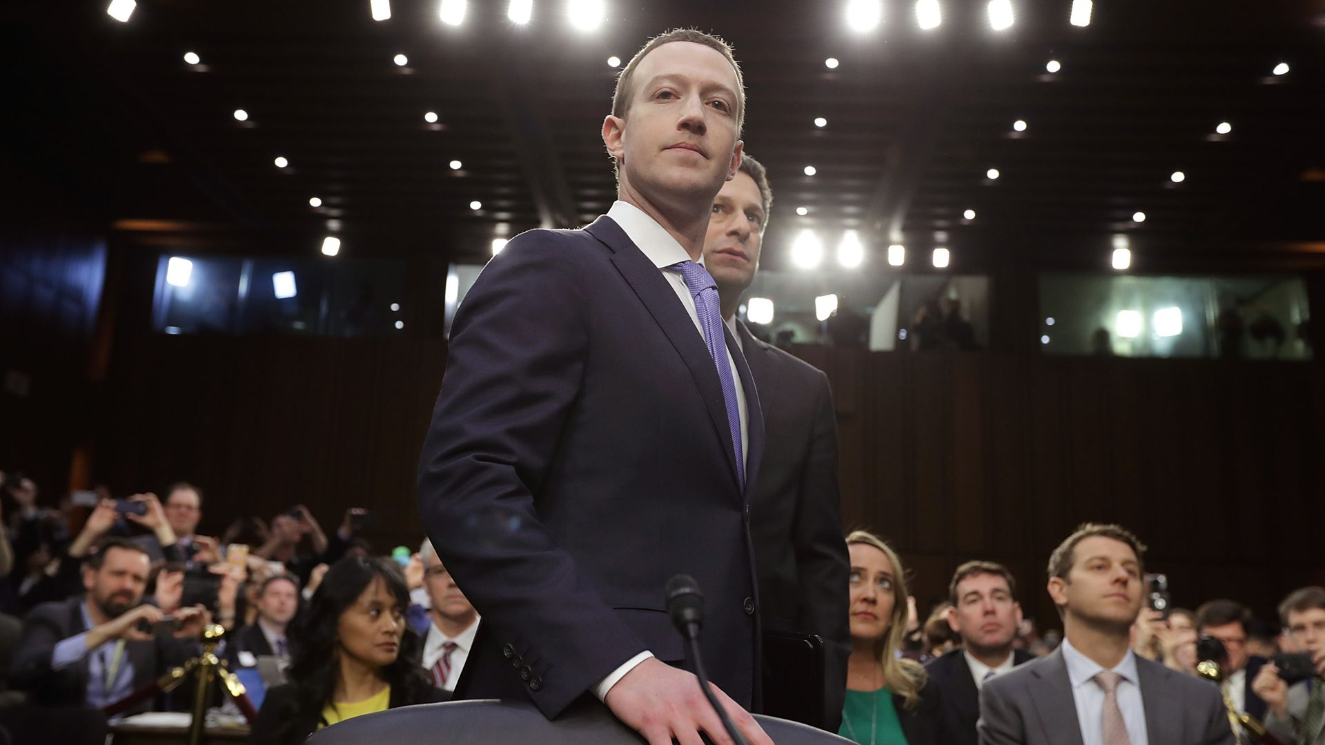Mark Zuckerberg stands with his hand on a chair