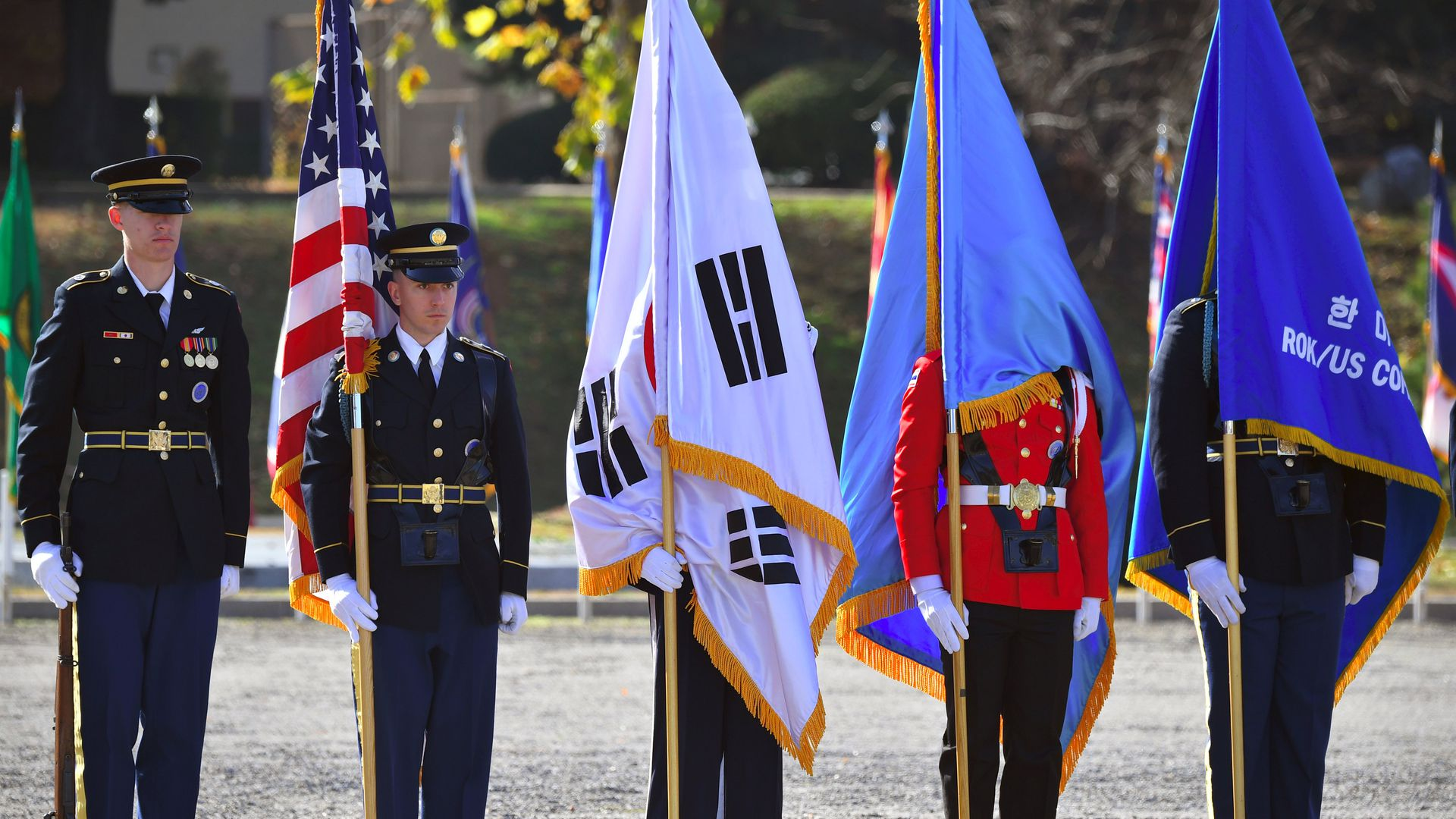 United Nations Command honour guards hold flags during a repatriation ceremony for the remains of an unidentified Korean War UN forces soldier at a US Army base in Seoul on November 20, 2018.