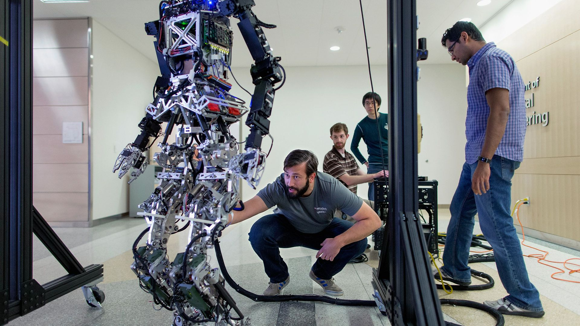 Photo of people adjusting a robot