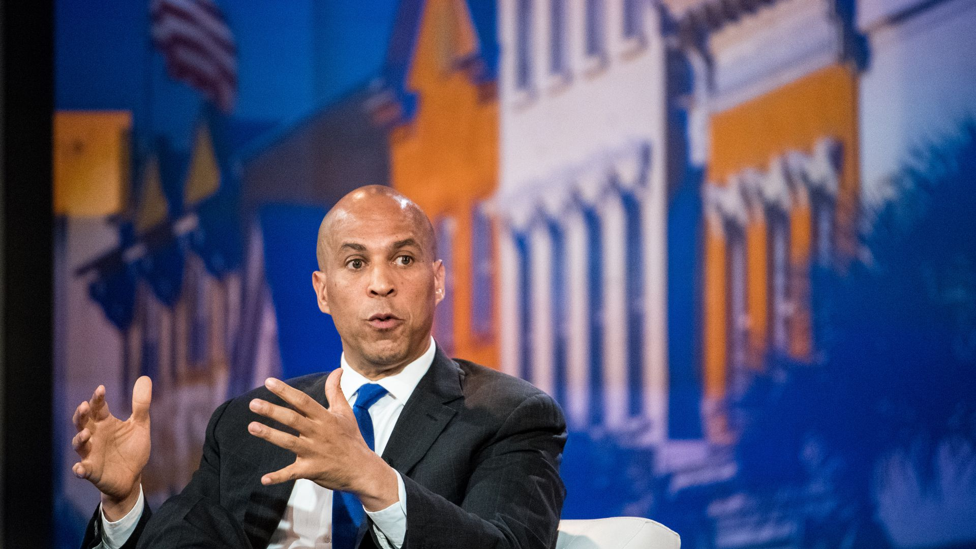 In this image, Booker sits while speaking.