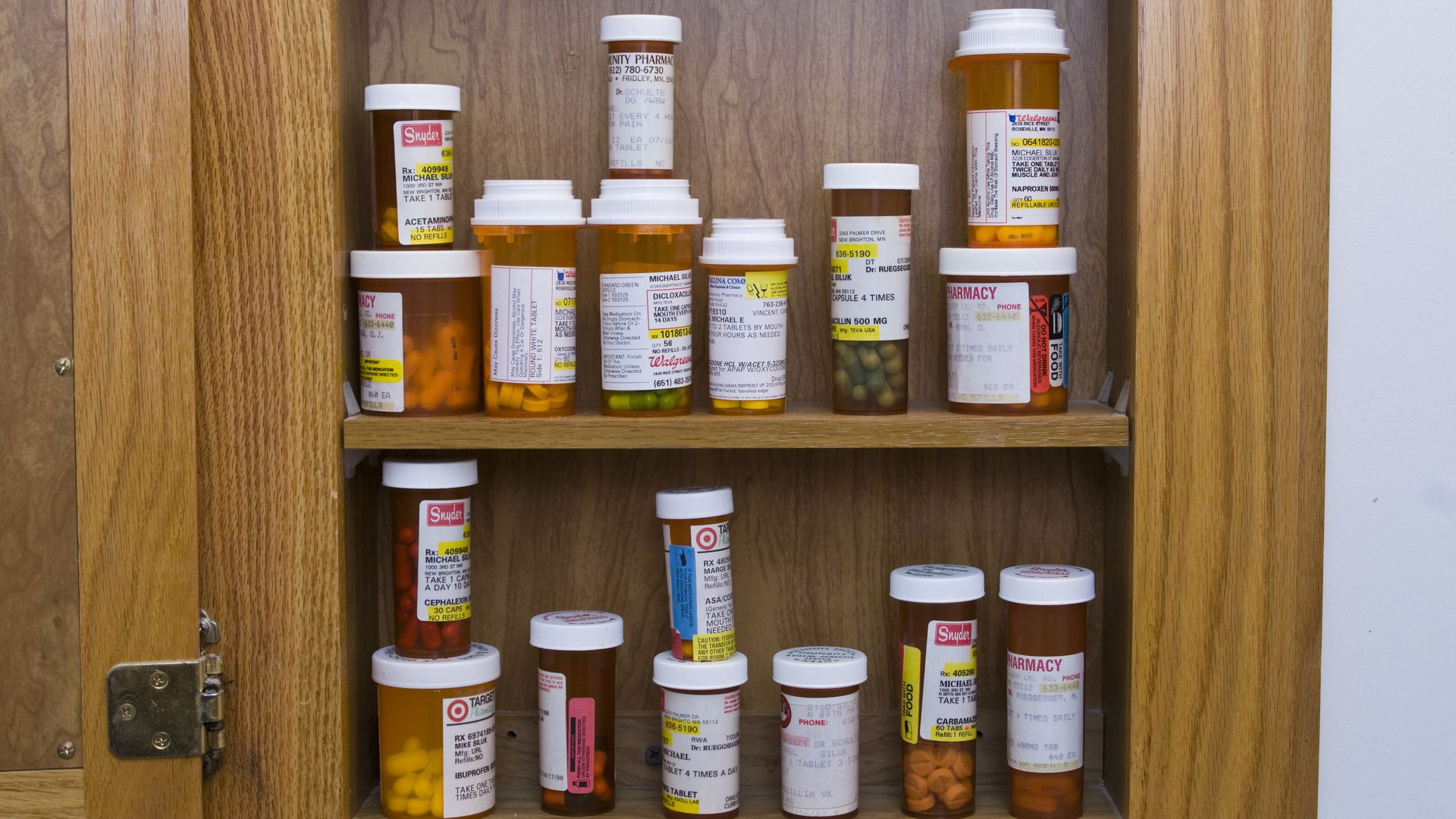 A medicine cabinet full of prescription bottles.
