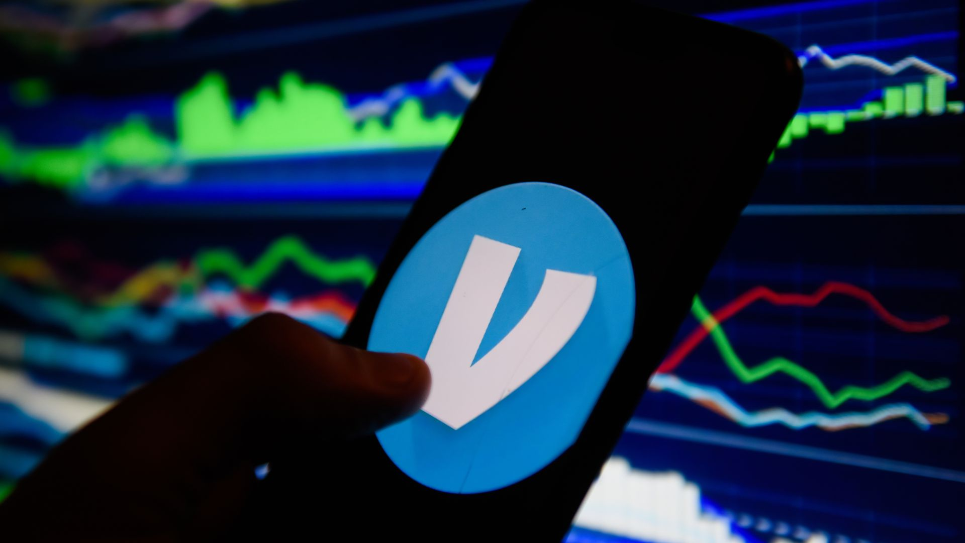 In this image, someone holds a smartphone with the Venmo logo displayed