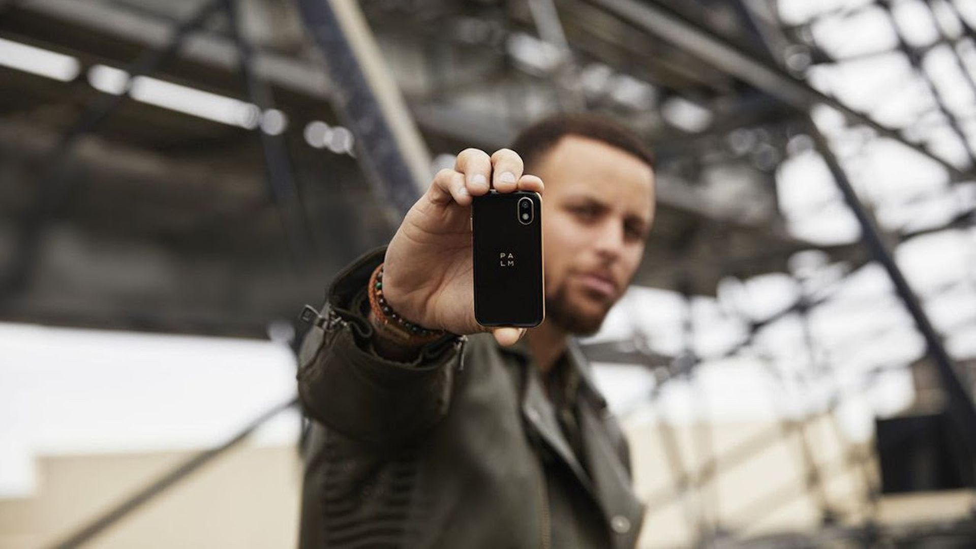 Steph Curry holding up a Palm phone.