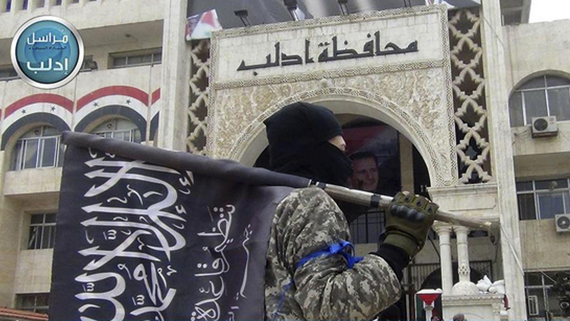 Masked al-Nusra fighter with flag